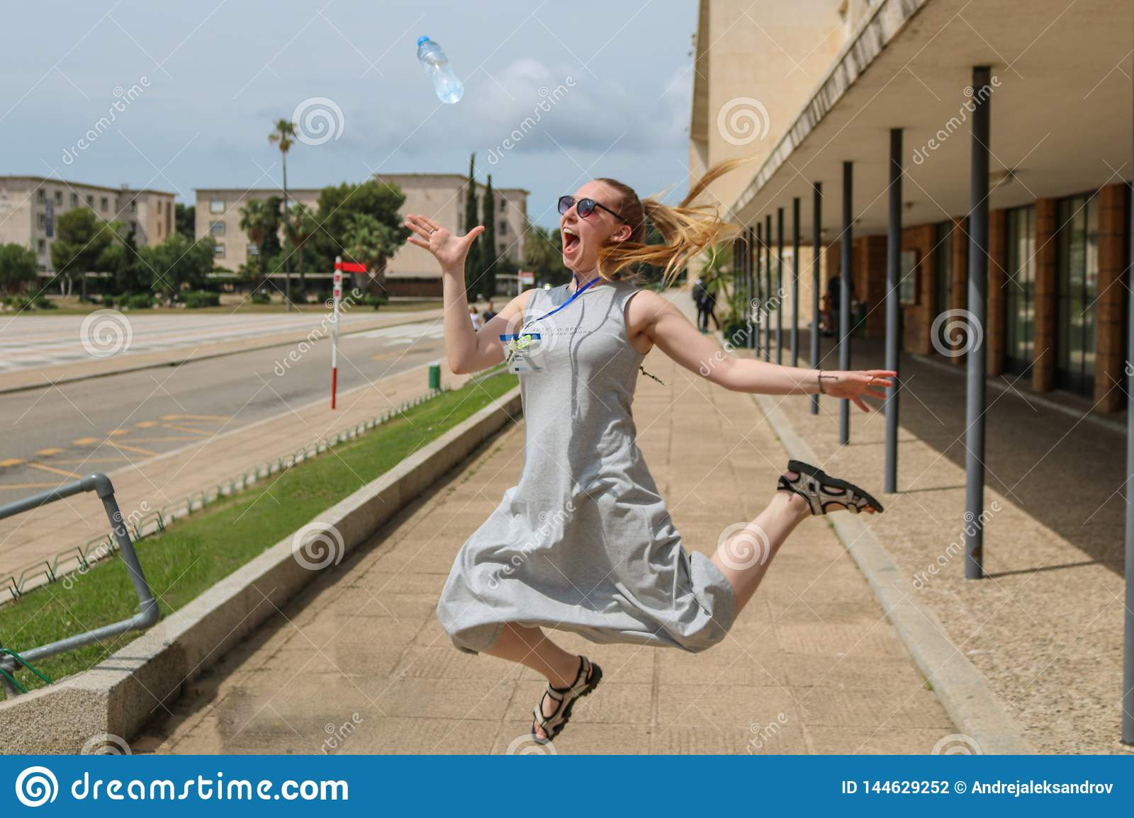 Blonde girl jumping, catching a water bottle