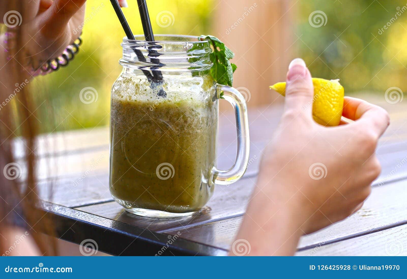 Shoothie fresco del limone in barattolo con paglia sulla tavola di legno