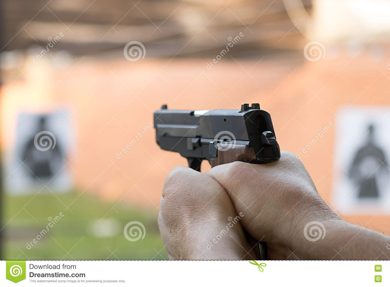 Shooting With A Pistol  Man Aiming Pistol In Shooting Range