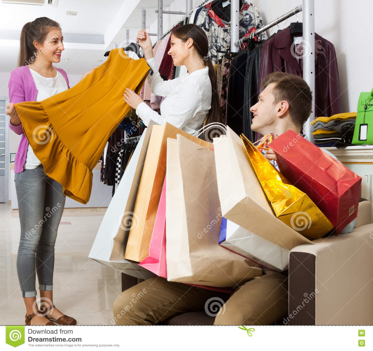 shop assistant in a clothing store offers young w dress stock shop assistant in a clothing store offers young w dress