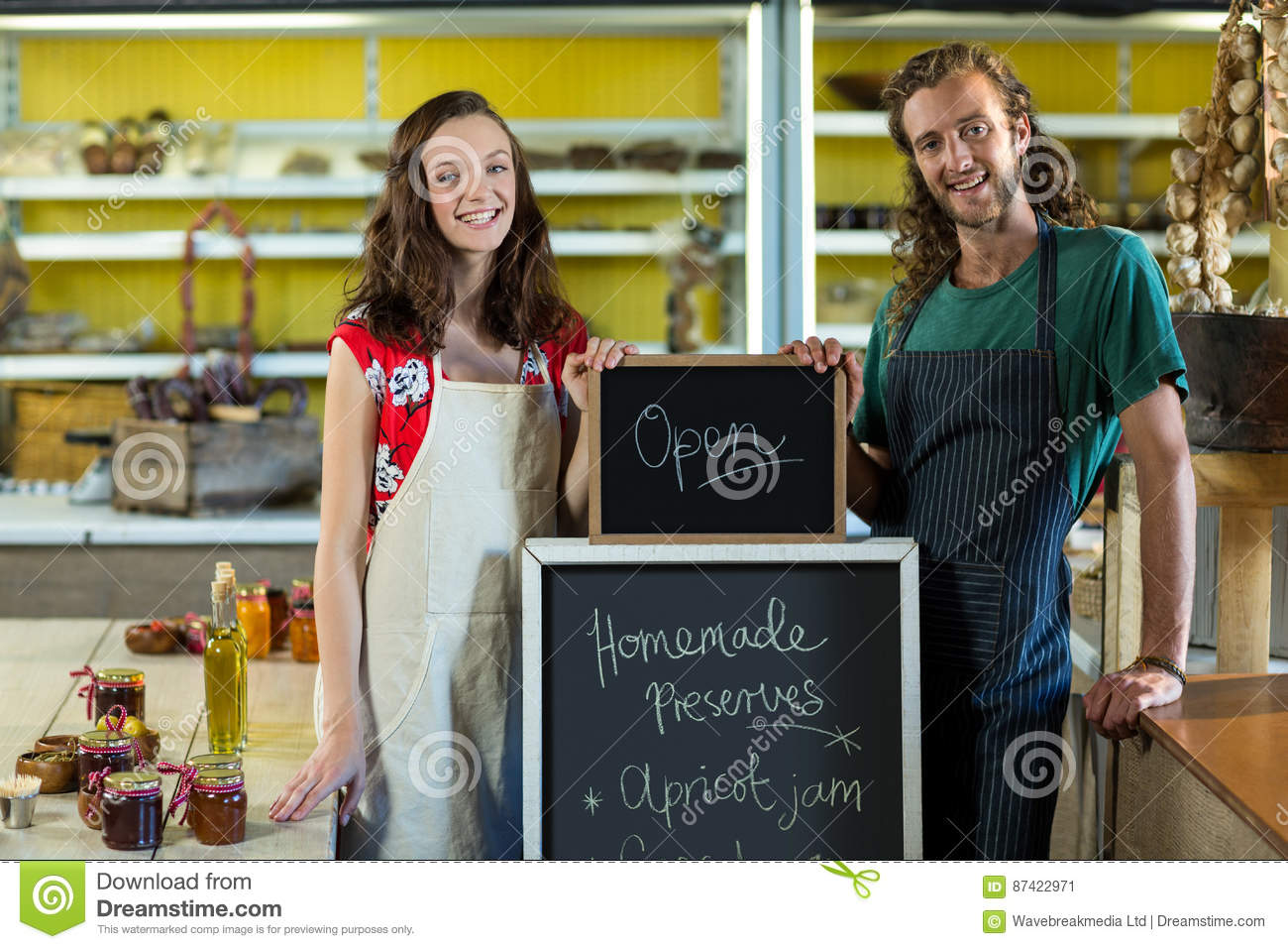 shop assistants holding open sign board