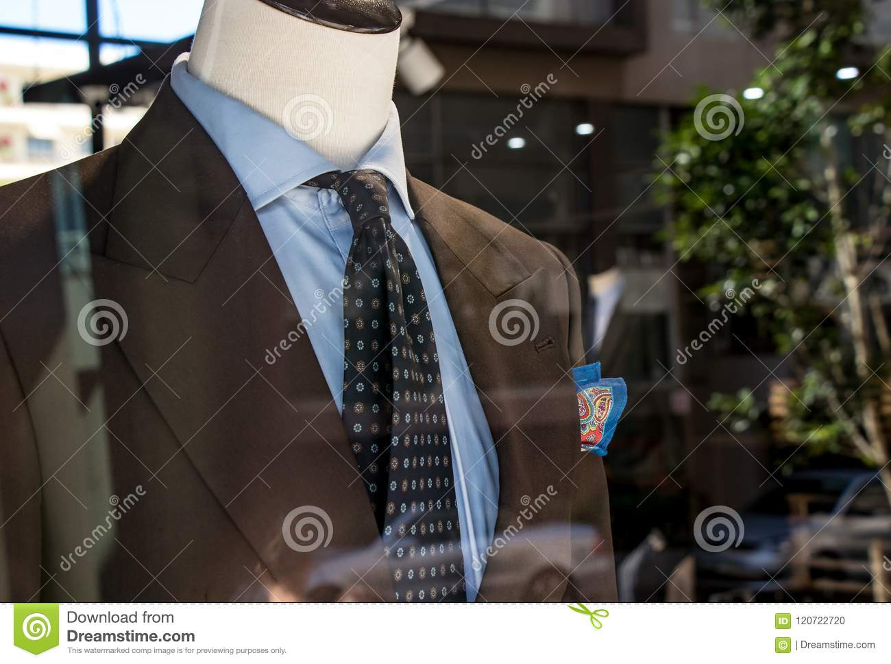 fcbf2d330 Shop window of mens tailor shop showing a mannequin in a brown tailored suit  and blue tie. Bright blue pocket handkerchief.