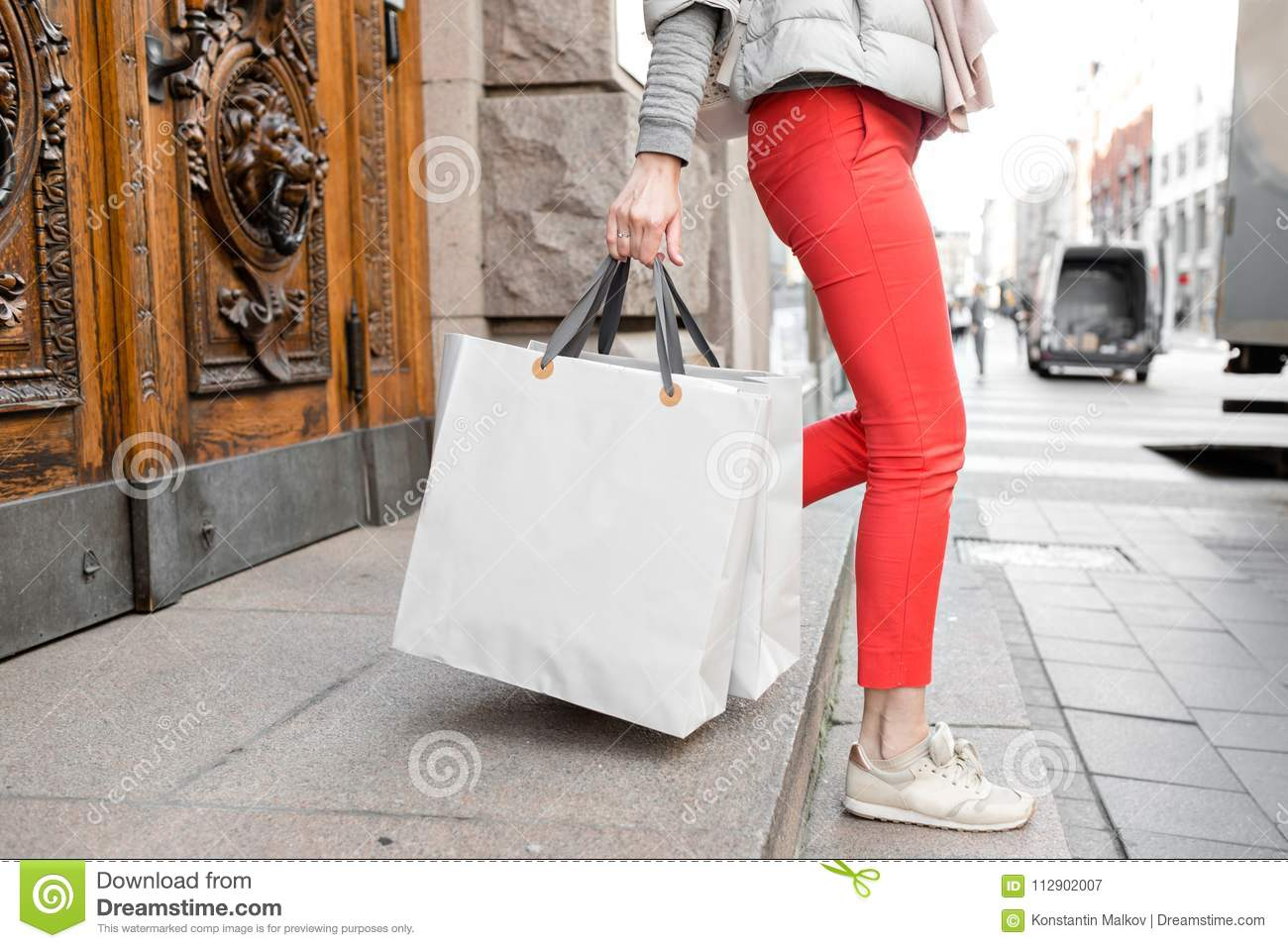 Shopaholic beautiful happy woman goes shopping in the city. Young girl in red pants and a lot of grey paper bags her