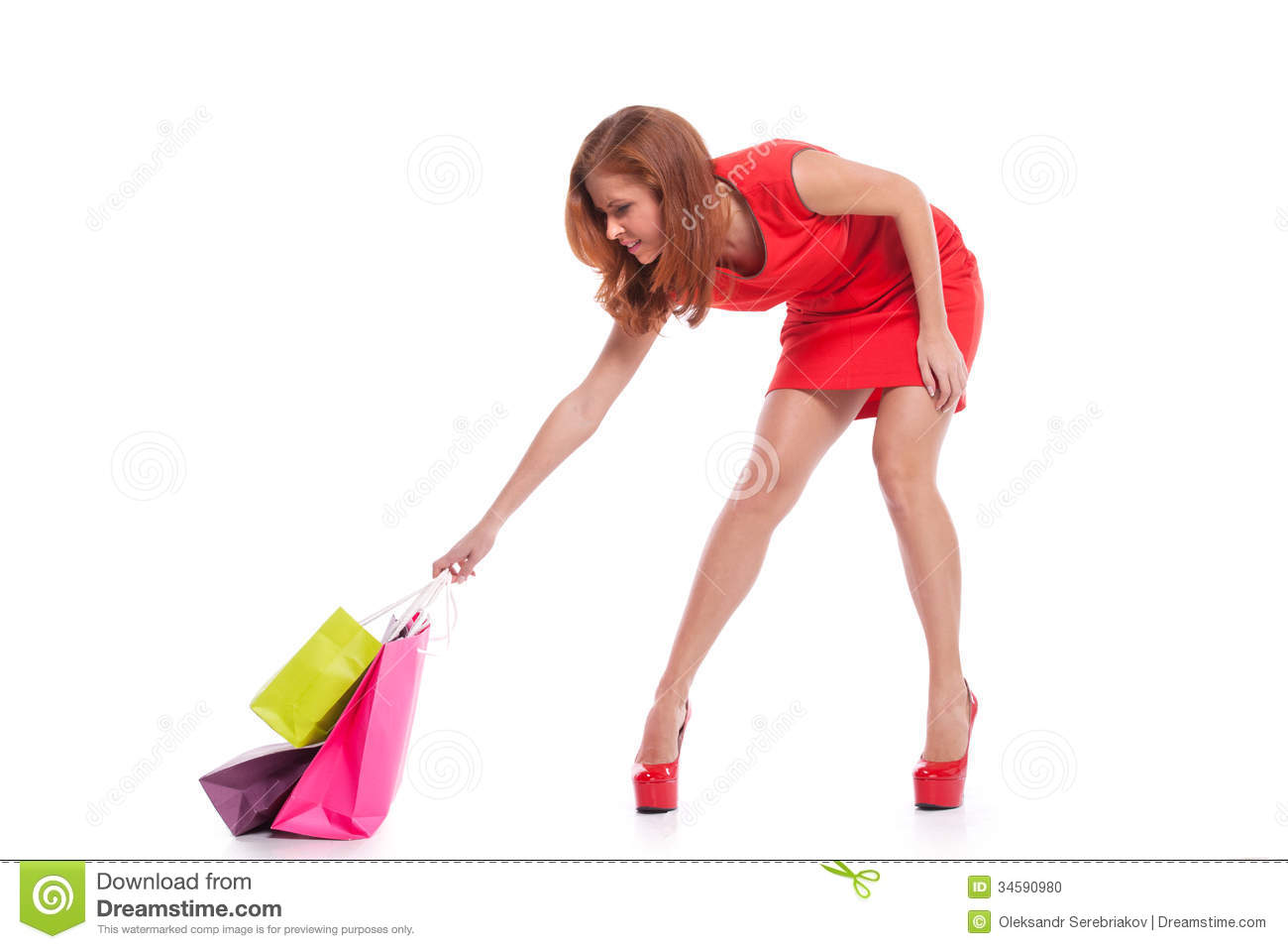 Young woman in red dress trying to lift shopping bags while standing ...