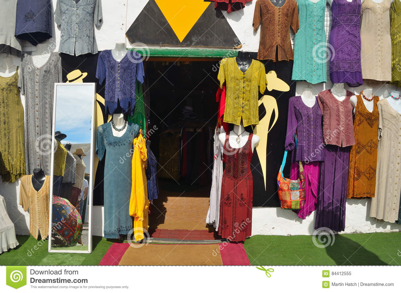 Shopfront with colorful garments hanging on wall and mirror.