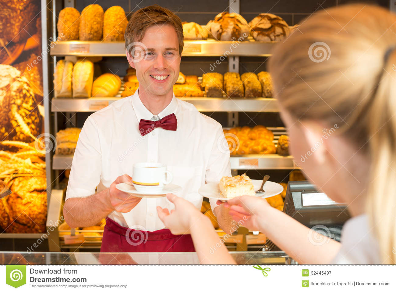 Shopkeeper In Cafe Giving Cup Of Coffee To Client Stock