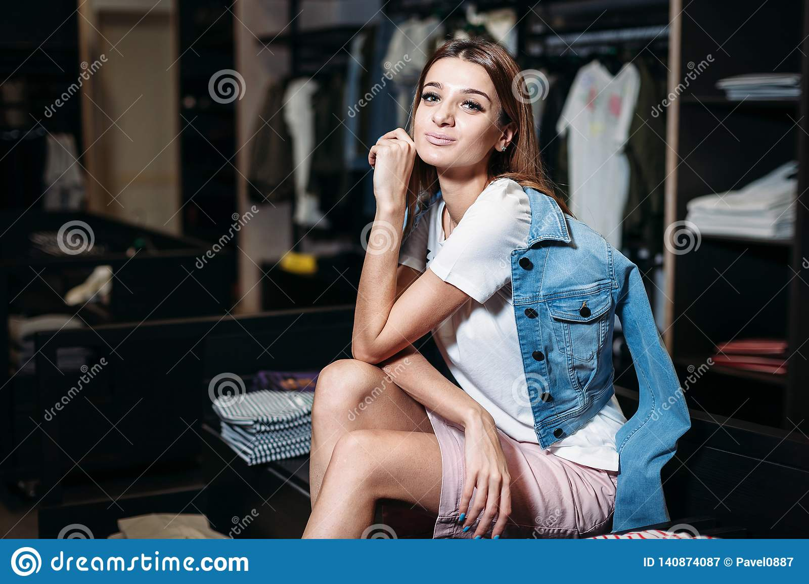 Shopping. Beautiful model brunette girl in stylish clothes, posing in clothing store, a new trend of clothes. Banner for a