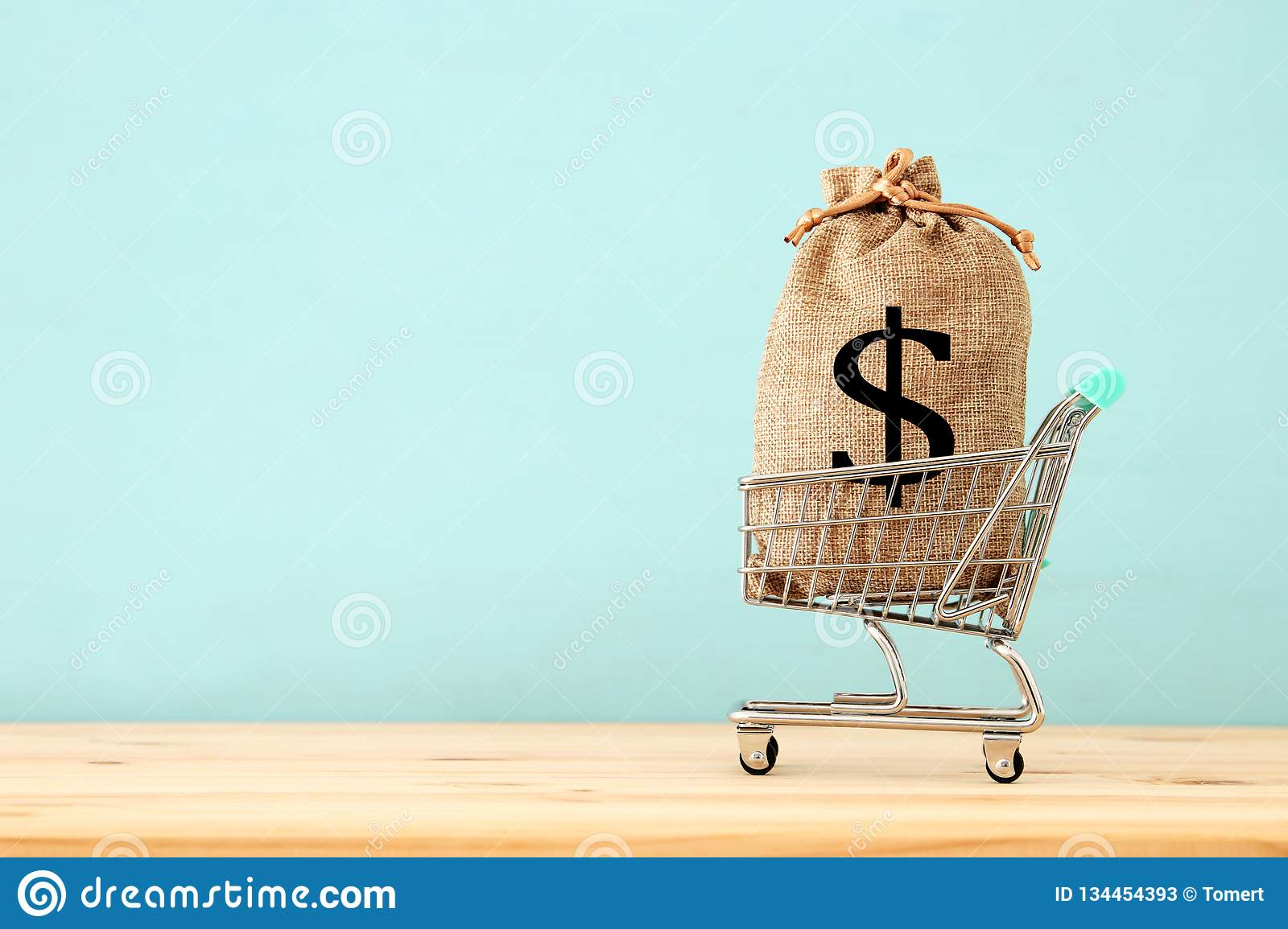 shopping cart with bag full of money with dollar sign over blue wooden background.
