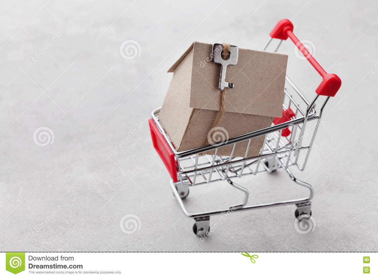 Shopping cart with model of cardboard house on gray background, buying a new home or sale of real estate concept