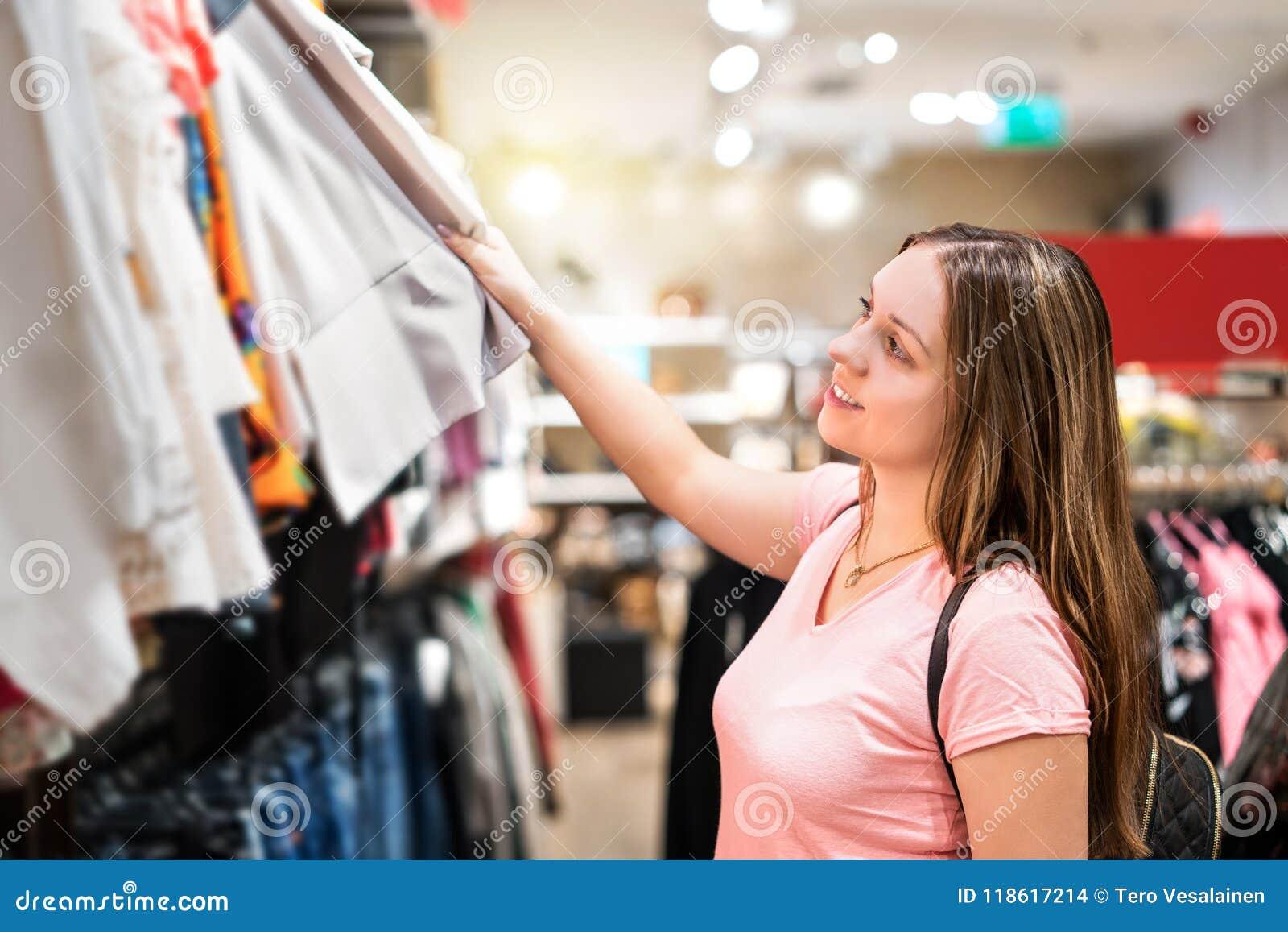 Shopping för ung kvinna i klädlager