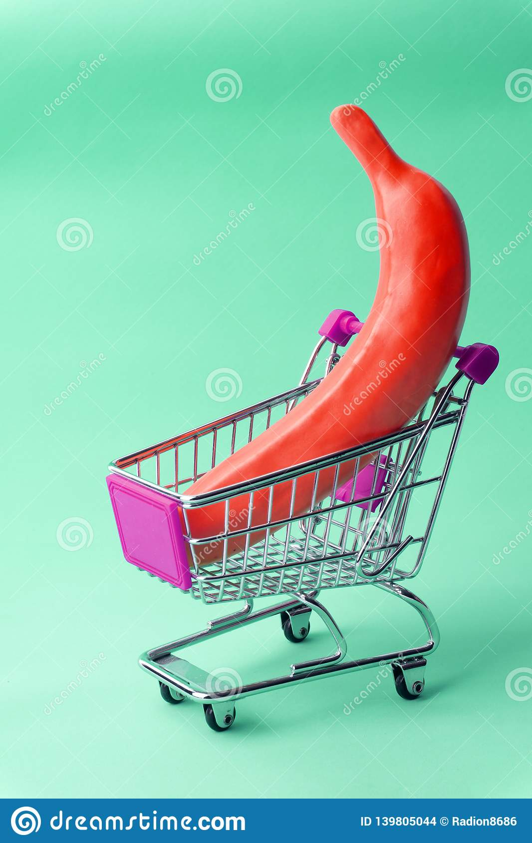 Shopping minimal concept. Banana in a toy shopping cart. Minimal pop art background, contemporary art.
