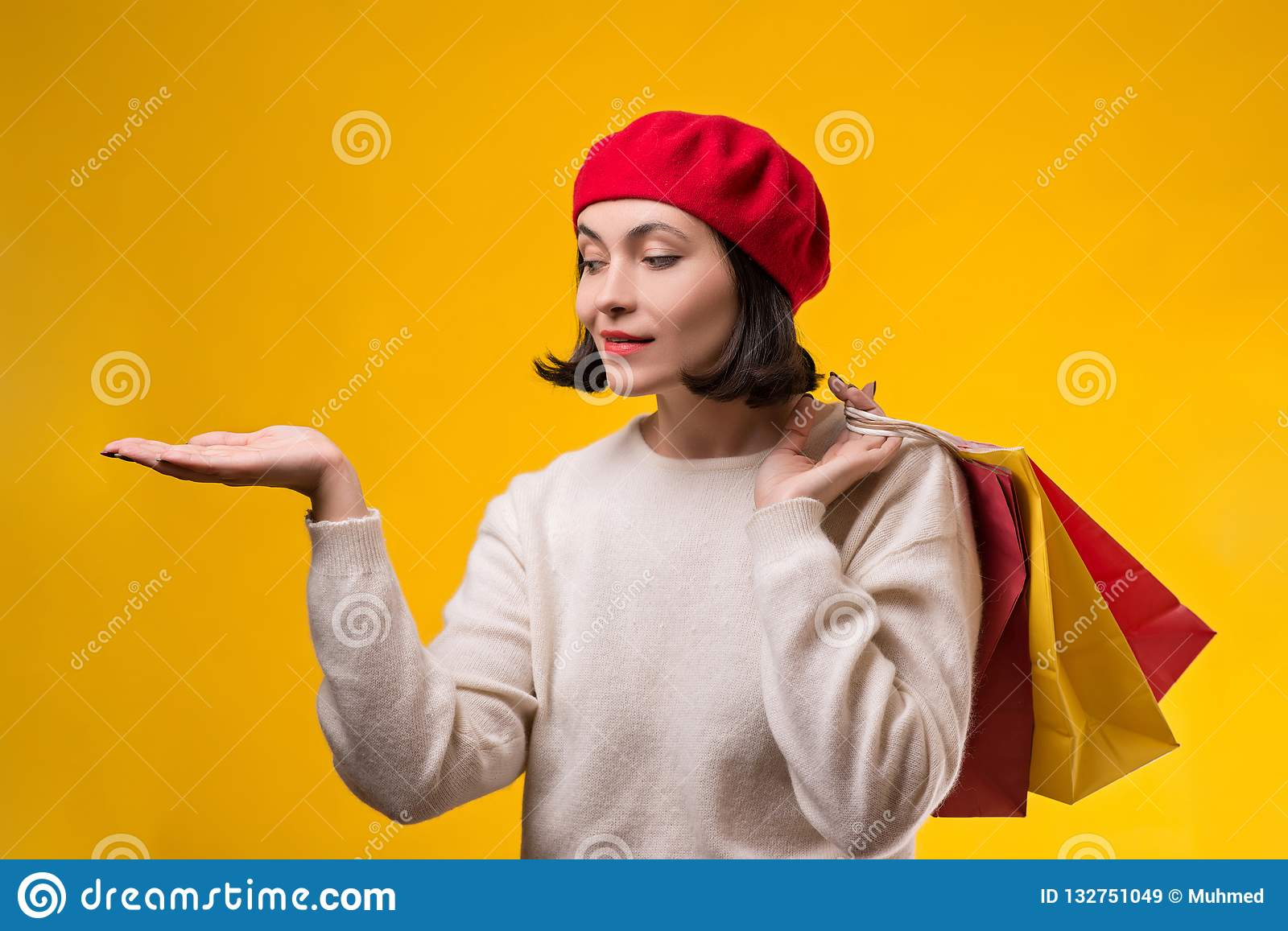Shopping woman showing something with open hand palm. Happy girl holding shopping bags. Fashion woman shopper isolated on yellow