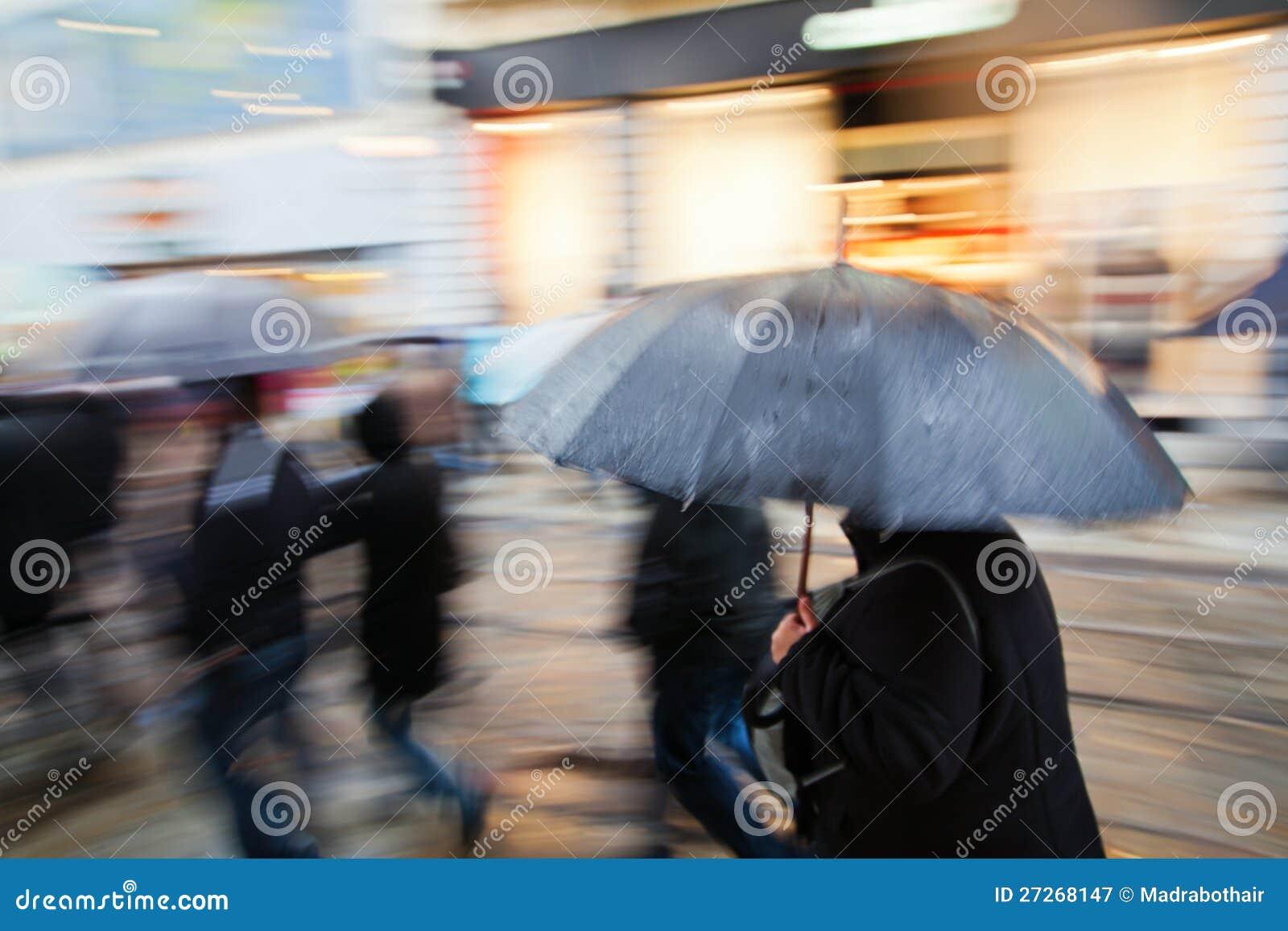 Shoppingfolk som går i den regniga staden