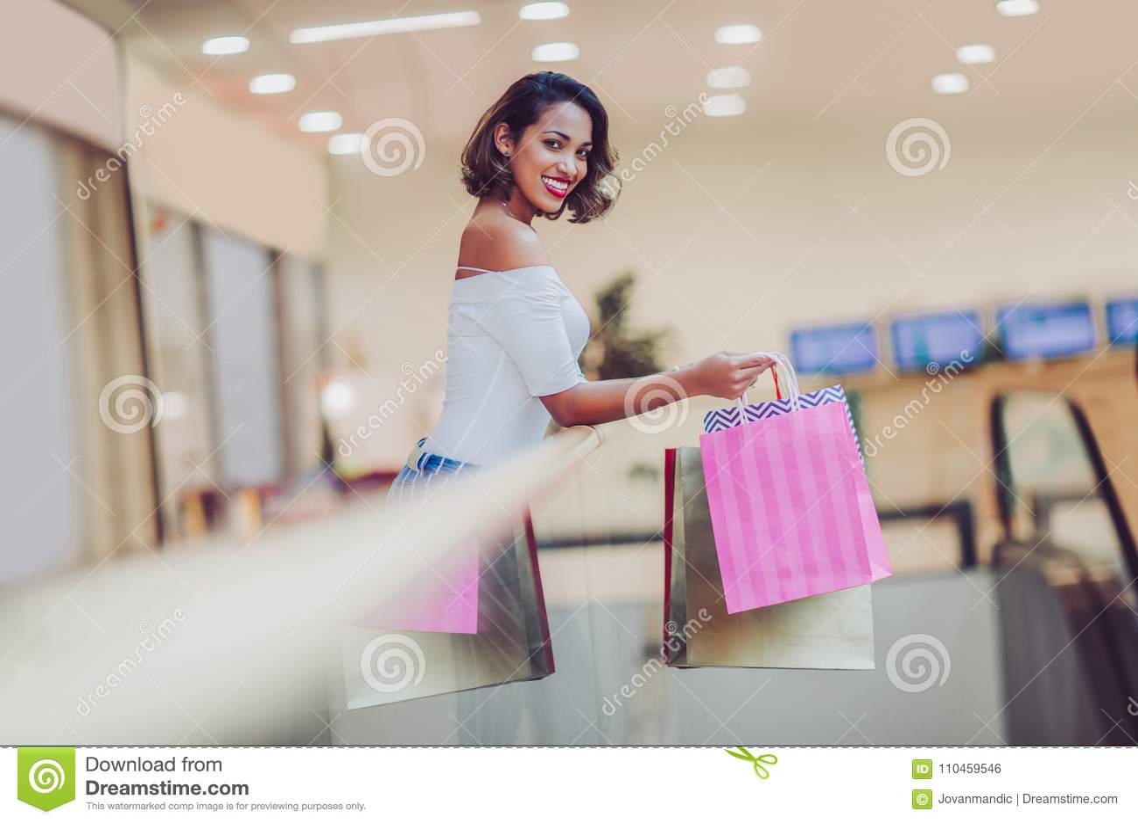 Shoppingkvinna som ler och rymmer påsar i shoppinggalleria