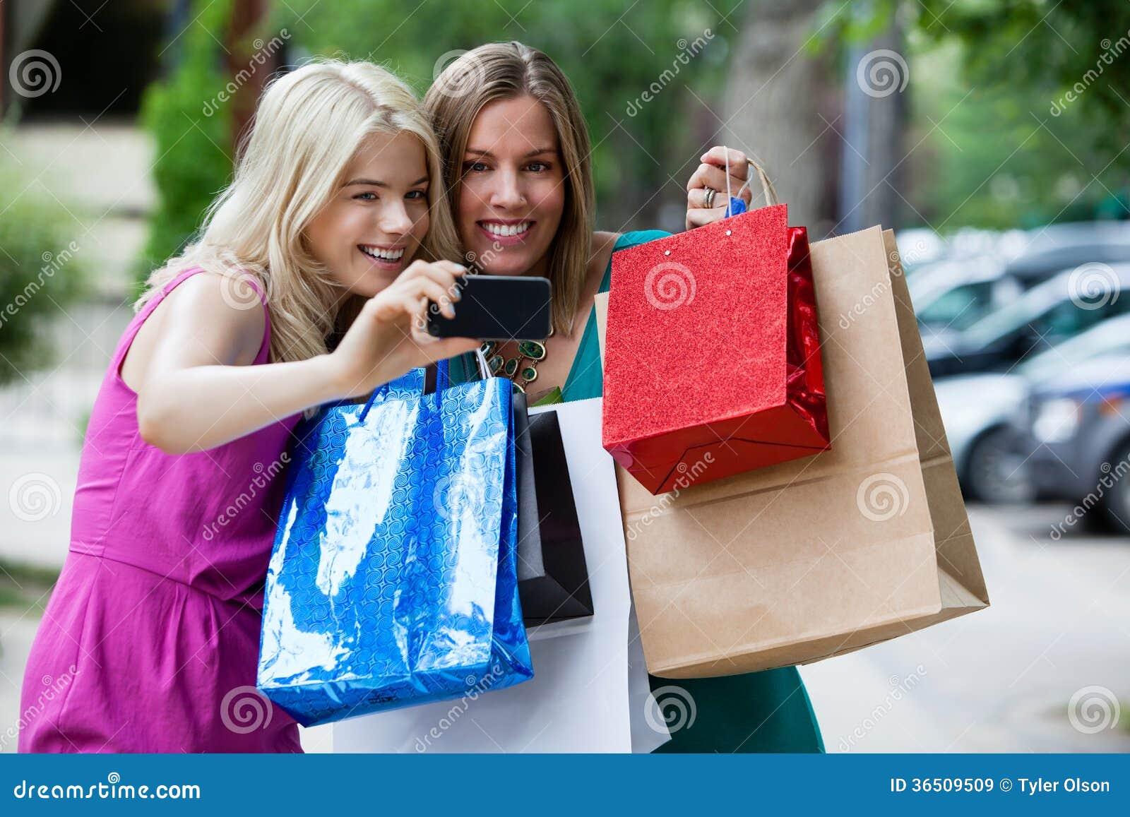 Shoppingkvinnor som tar fotografiet