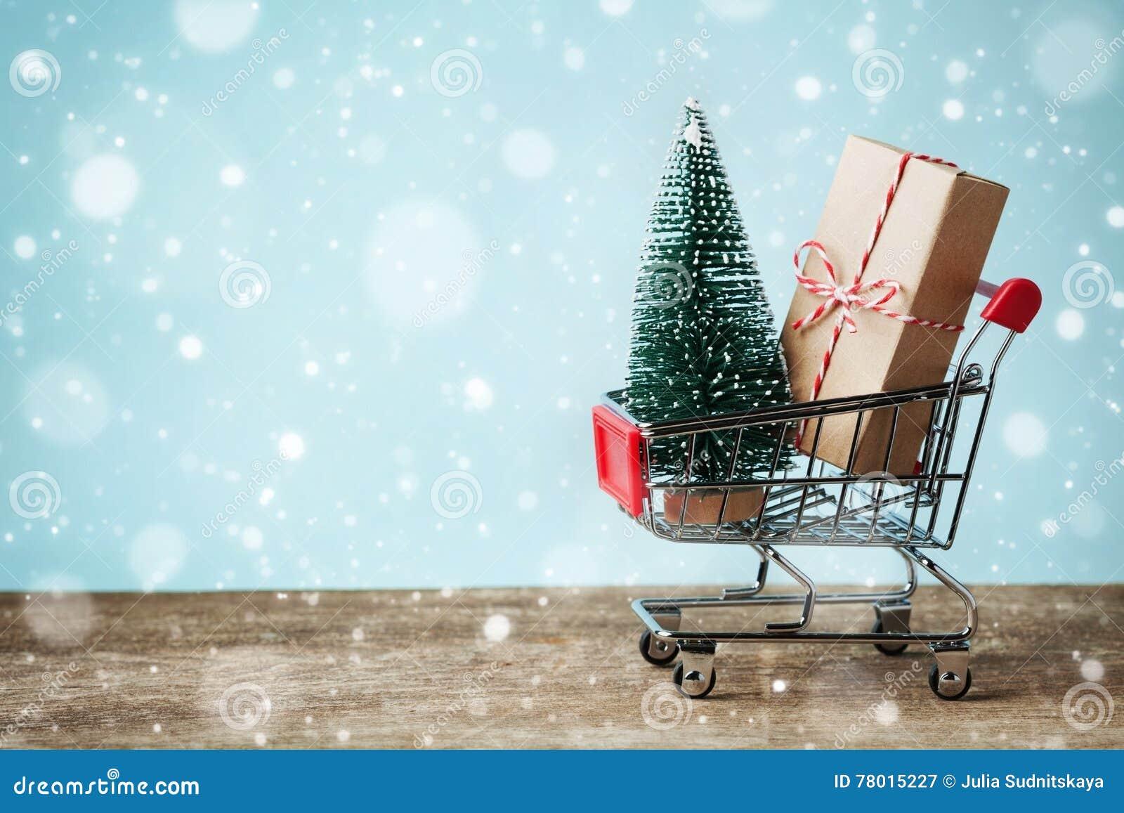 Shoppingvagn med gåva- eller gåva- och granträdet på snöig effektbakgrund Jul och försäljningsbegrepp för nytt år greeting lyckli