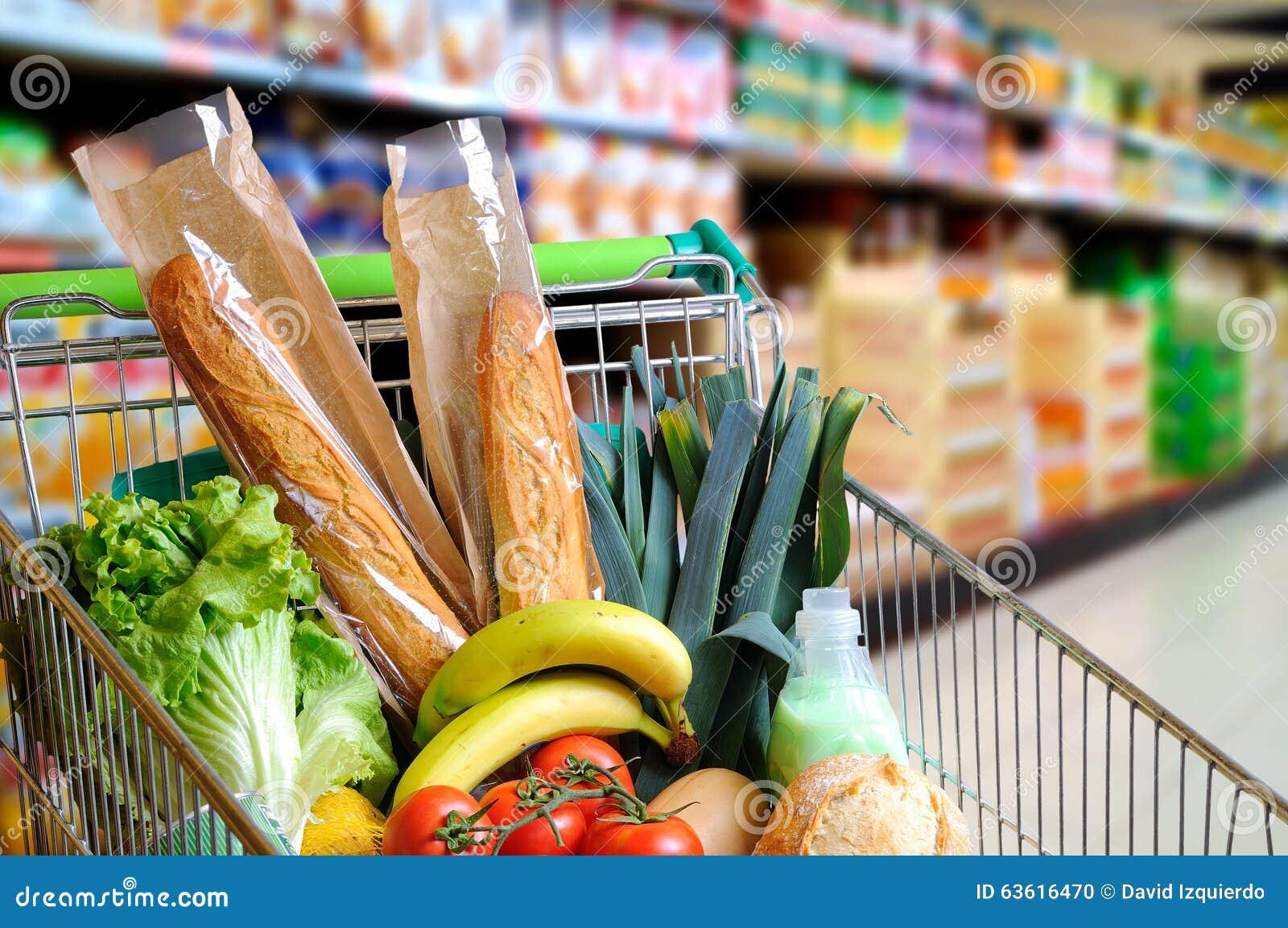 Shoppingvagnen av mat i supermarketgång höjde mycket sikt