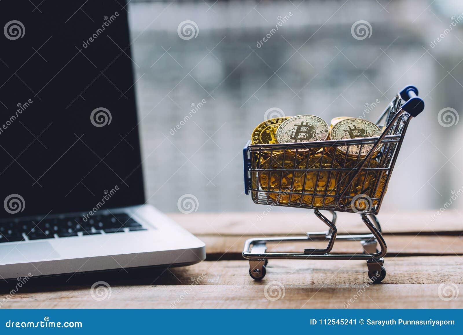 Shoppingvagnen fyllde med högar av cryptocurrencybitcoinmynt med datorbärbara datorn som var närliggande på träplattformen