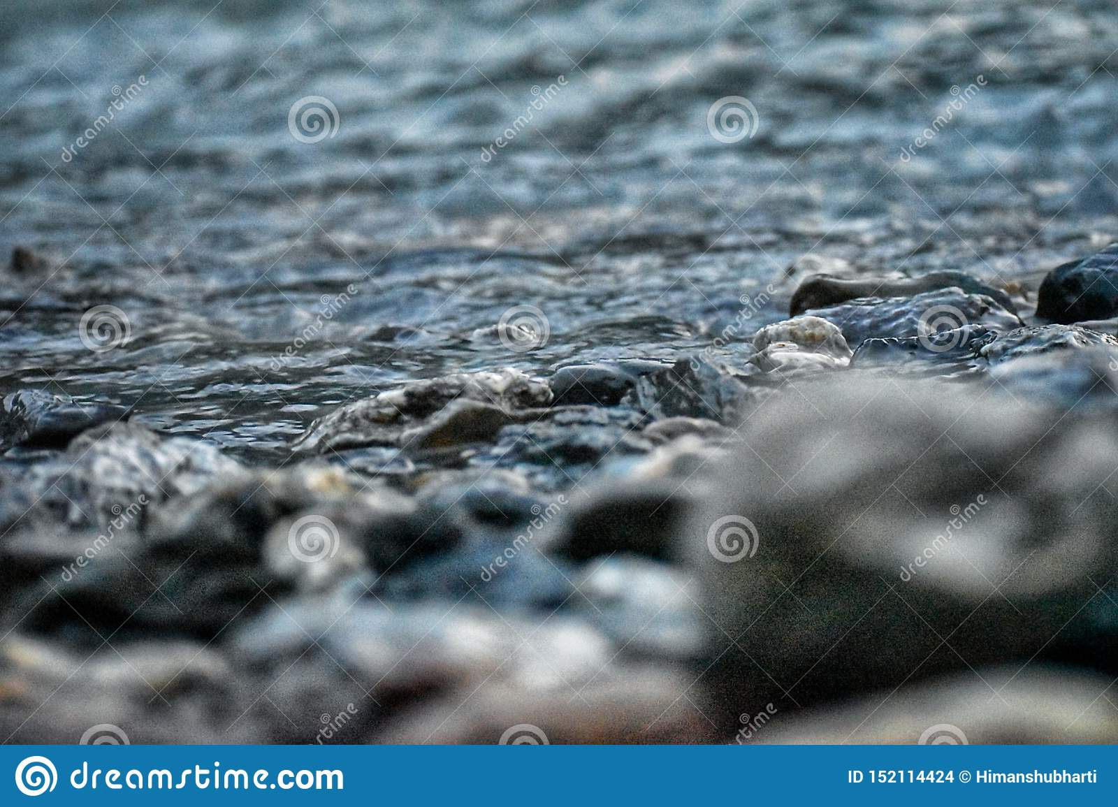 Shore of a river with stones and water with blur front view