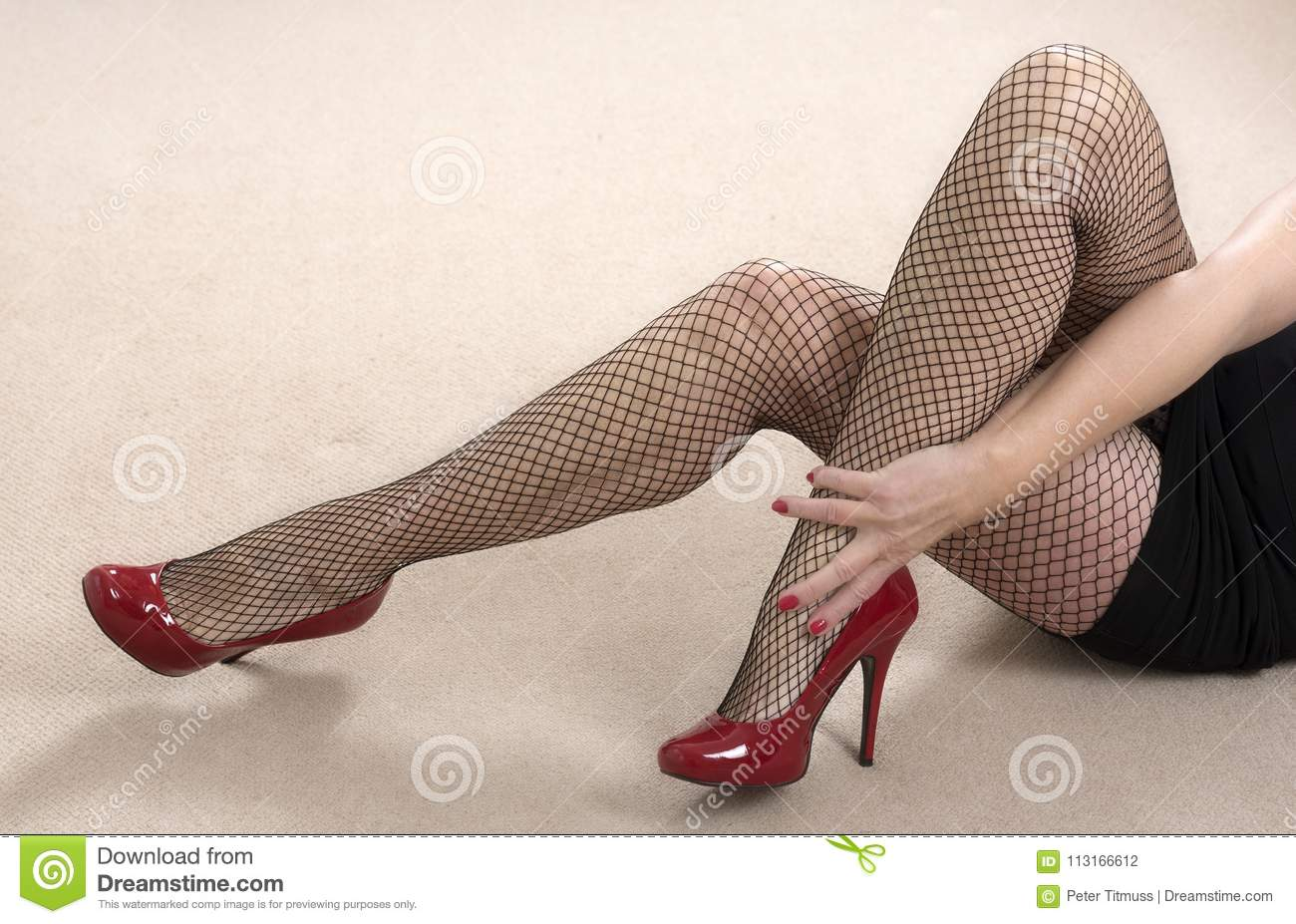 6252057d6768 Portrait of a mature woman wearing black fishnet tights and red shoes