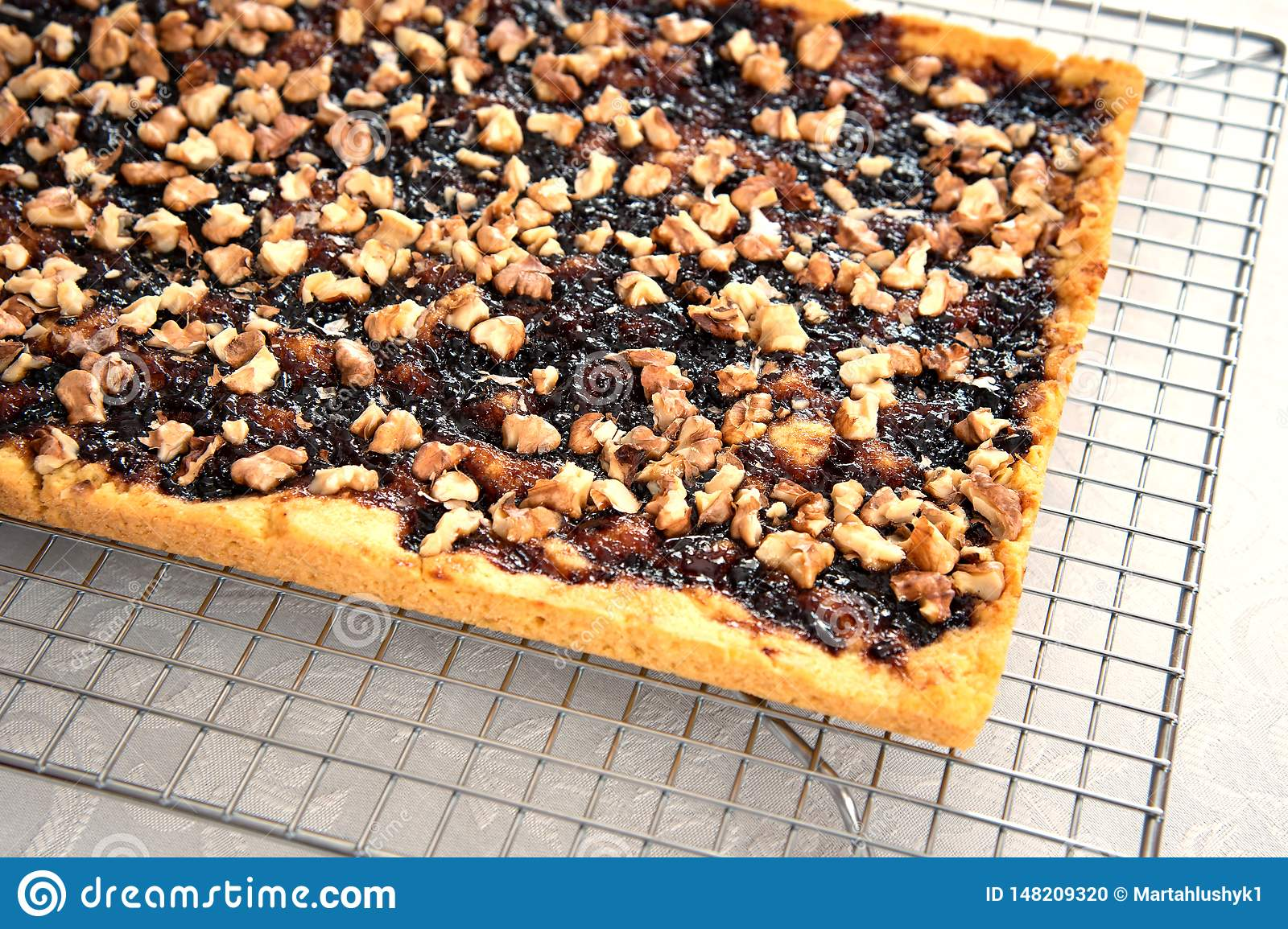 Shortbread pie with jam and walnuts on cooling rack