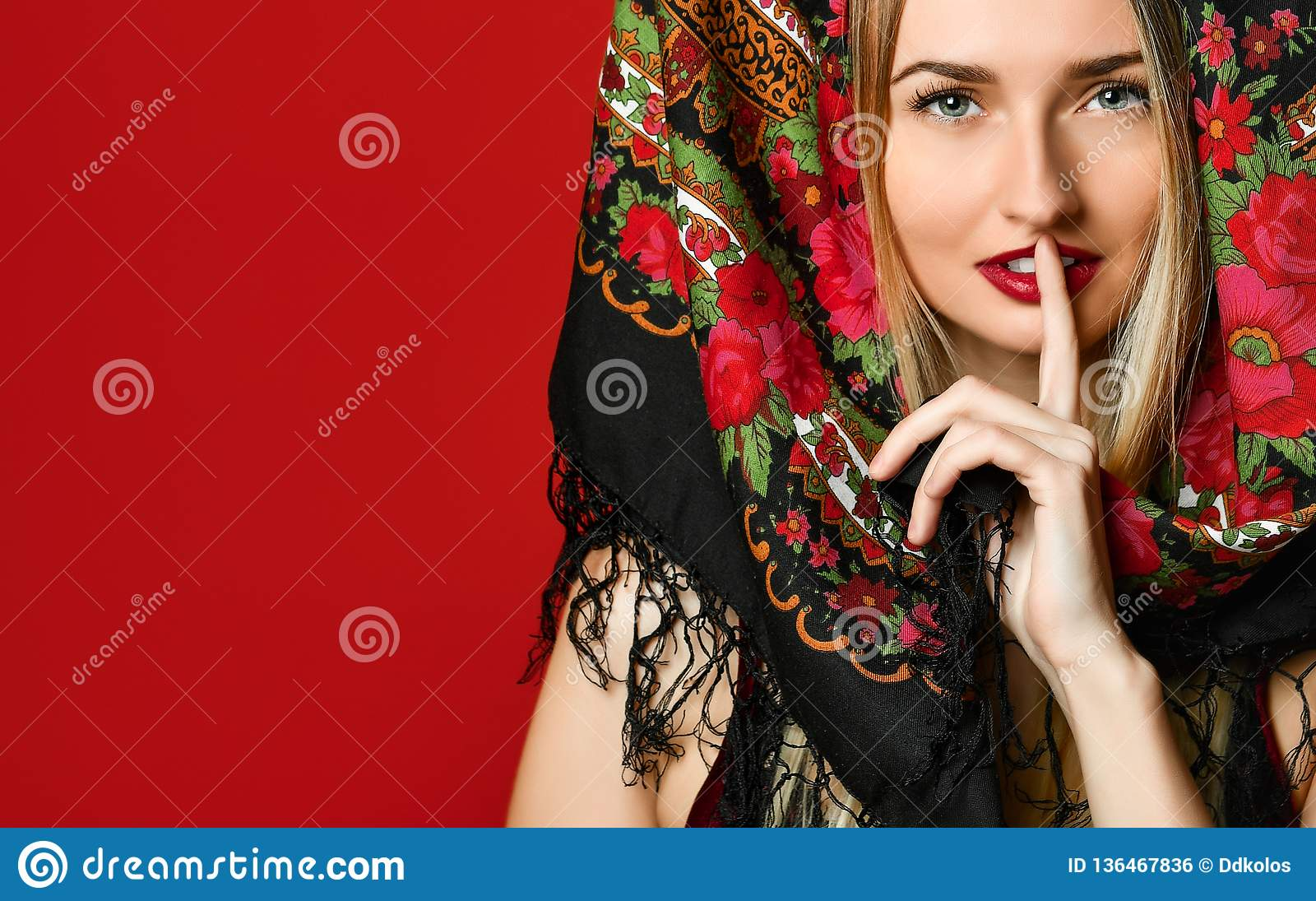 Shot of beautiful female with long blonde hair wears kokoshnik cap and patterned shawl, shows hush sign