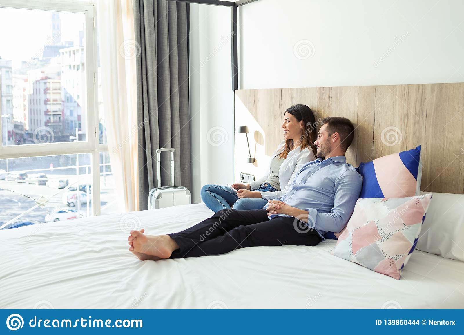 Beautiful lovely young couple lying and relaxing on bed looking sideways at hotel room