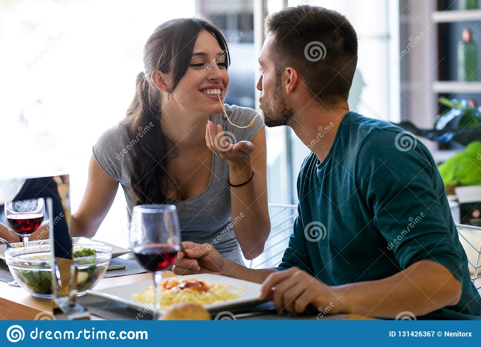 Beautiful young couple sharing single spaghetti getting closer to kissing in the kitchen at home