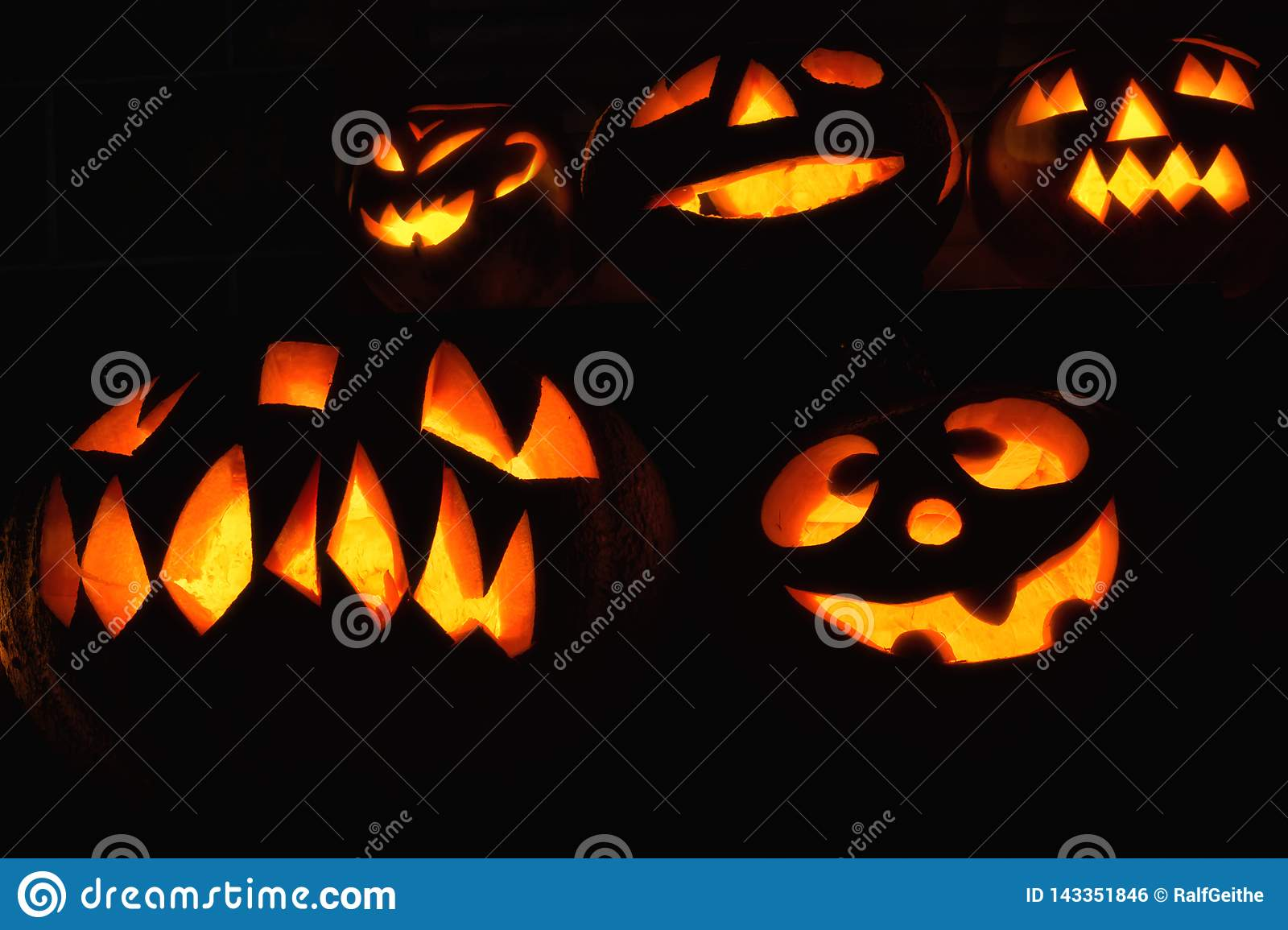 Various creatively carved pumpkins in the dark for Halloween
