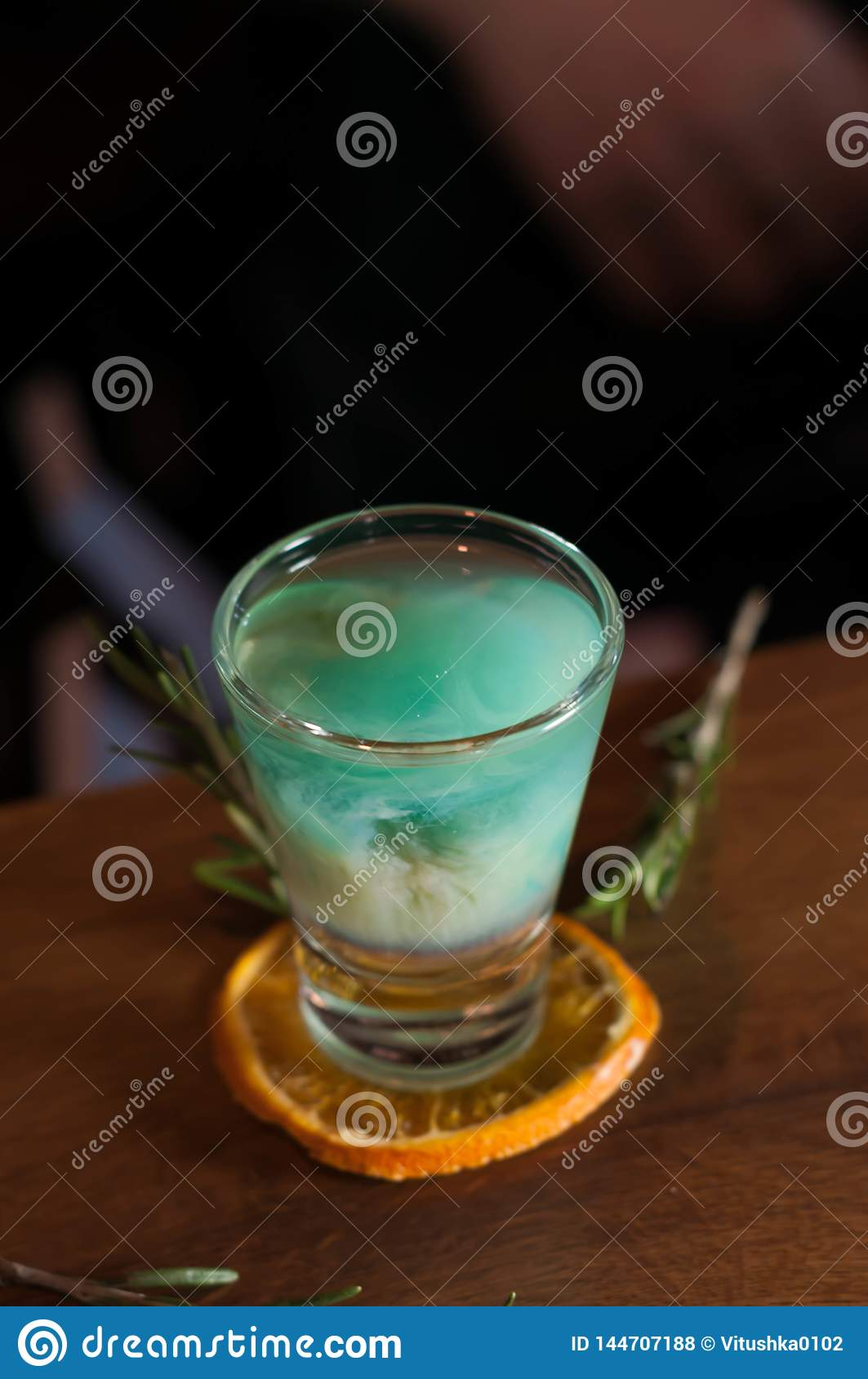 Shot glass with blue alcohol drink on dried orange slice with rosemary