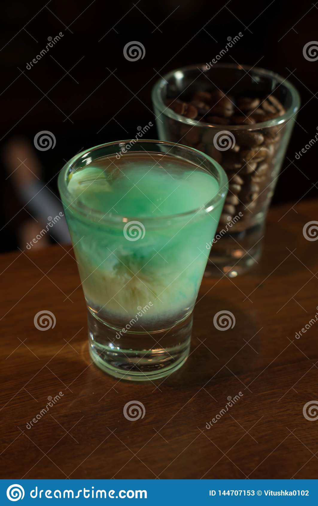Shot glass with blue alcohol drink near glass with coffee beans
