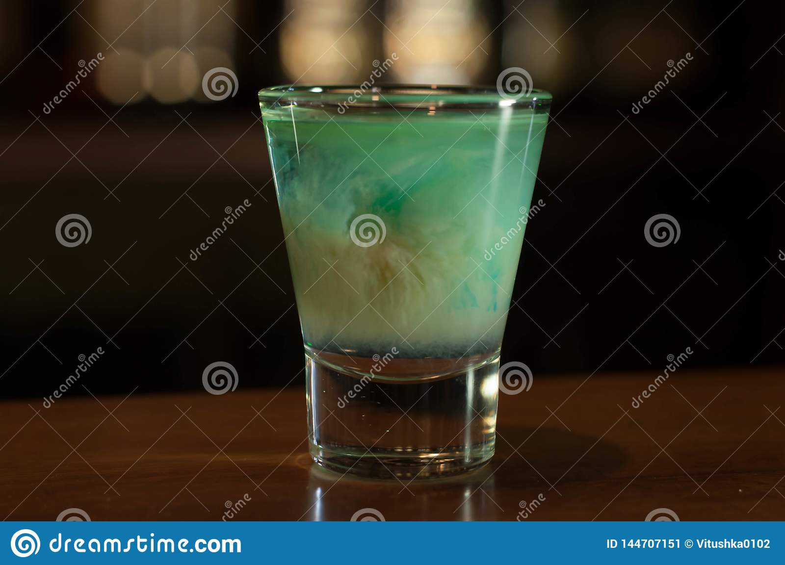 Shot glass with blue alcohol drink on wooden table in bar