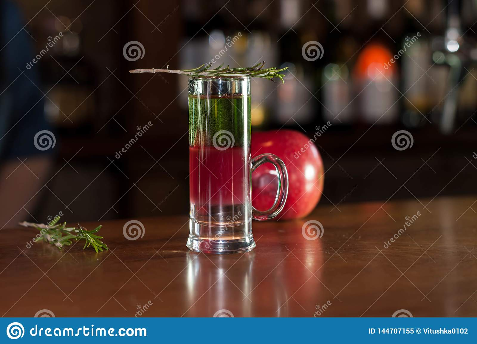 Shot glass with multicolored alcohol drink and rosemary on near red apple