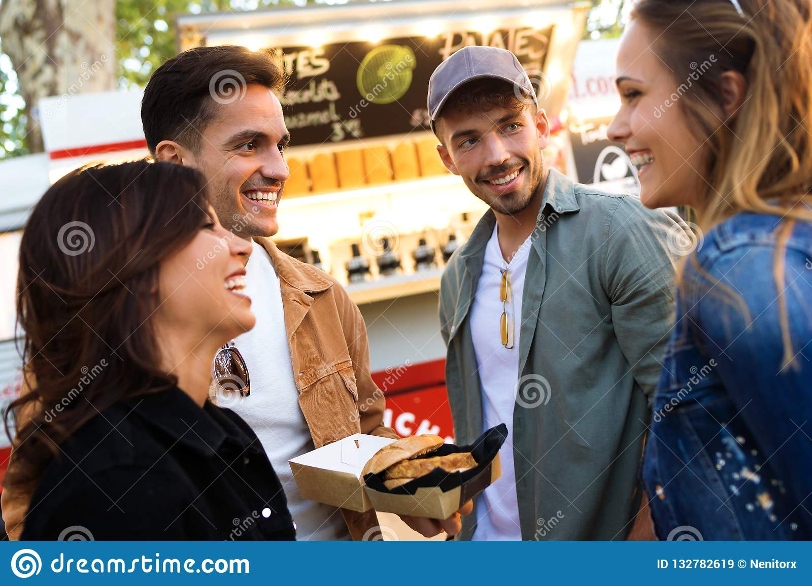 Group of attractive young friends talking while visiting eat market in the street.