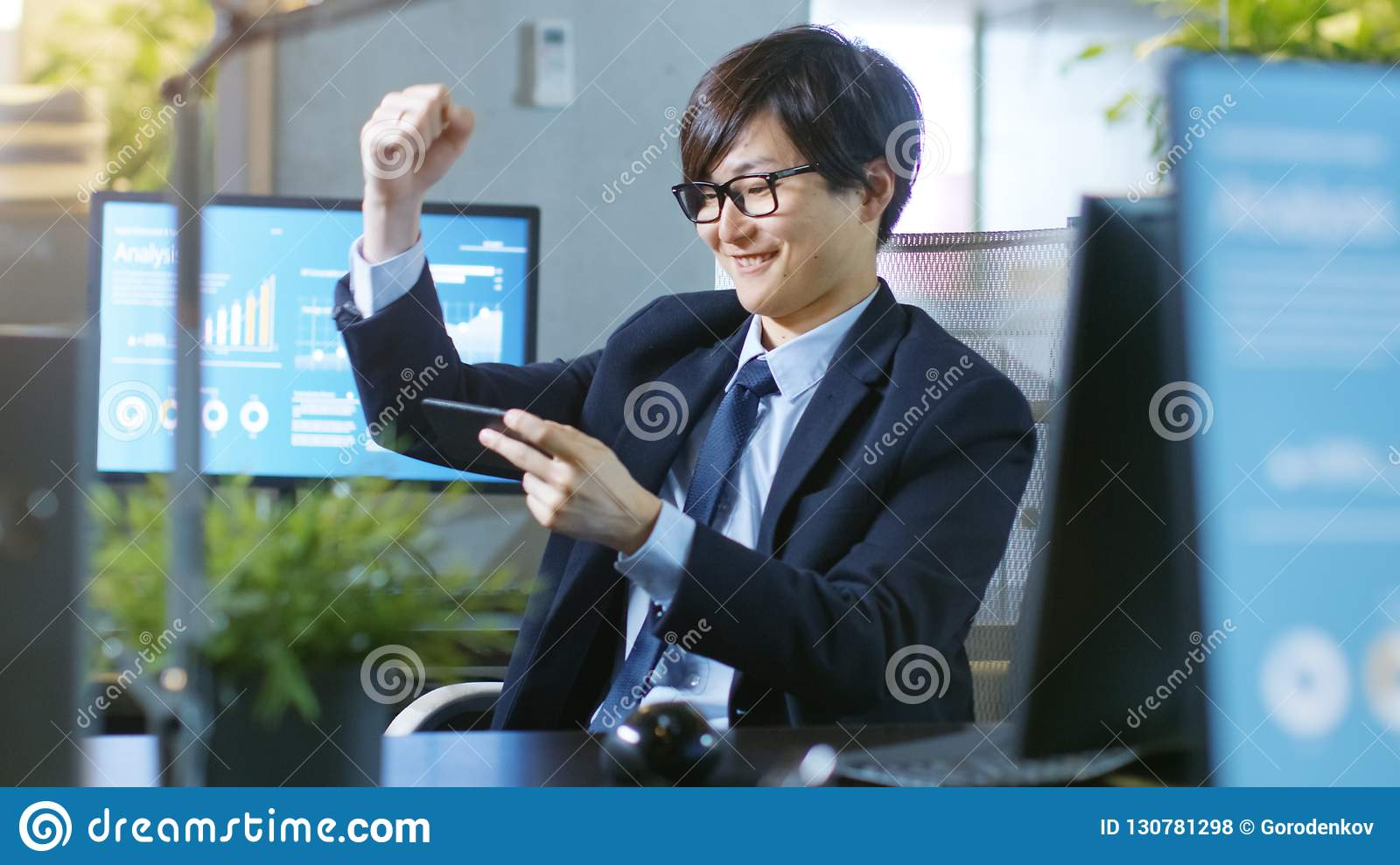 Shot of the Happy East Asian Businessman Winning in Mobile Game