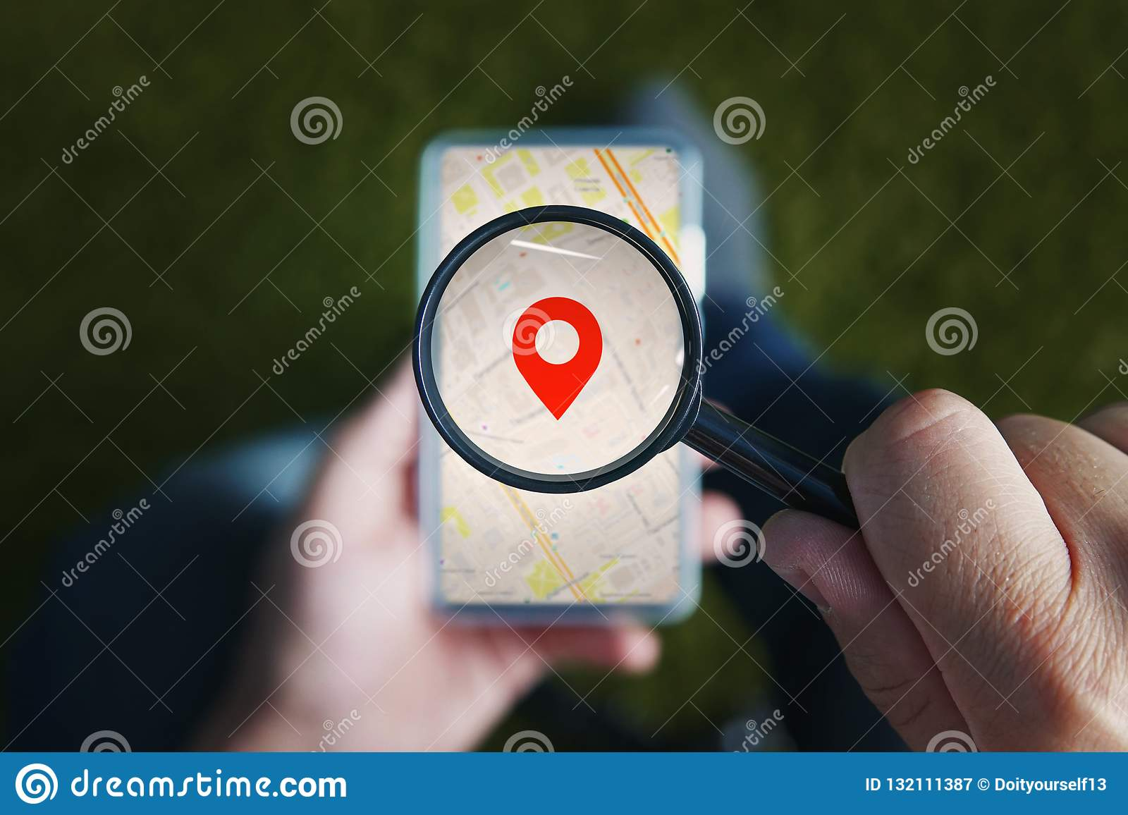 Shot of male hands holding magnifying glass with the red icon of geo-location and looking through it to the smartphone