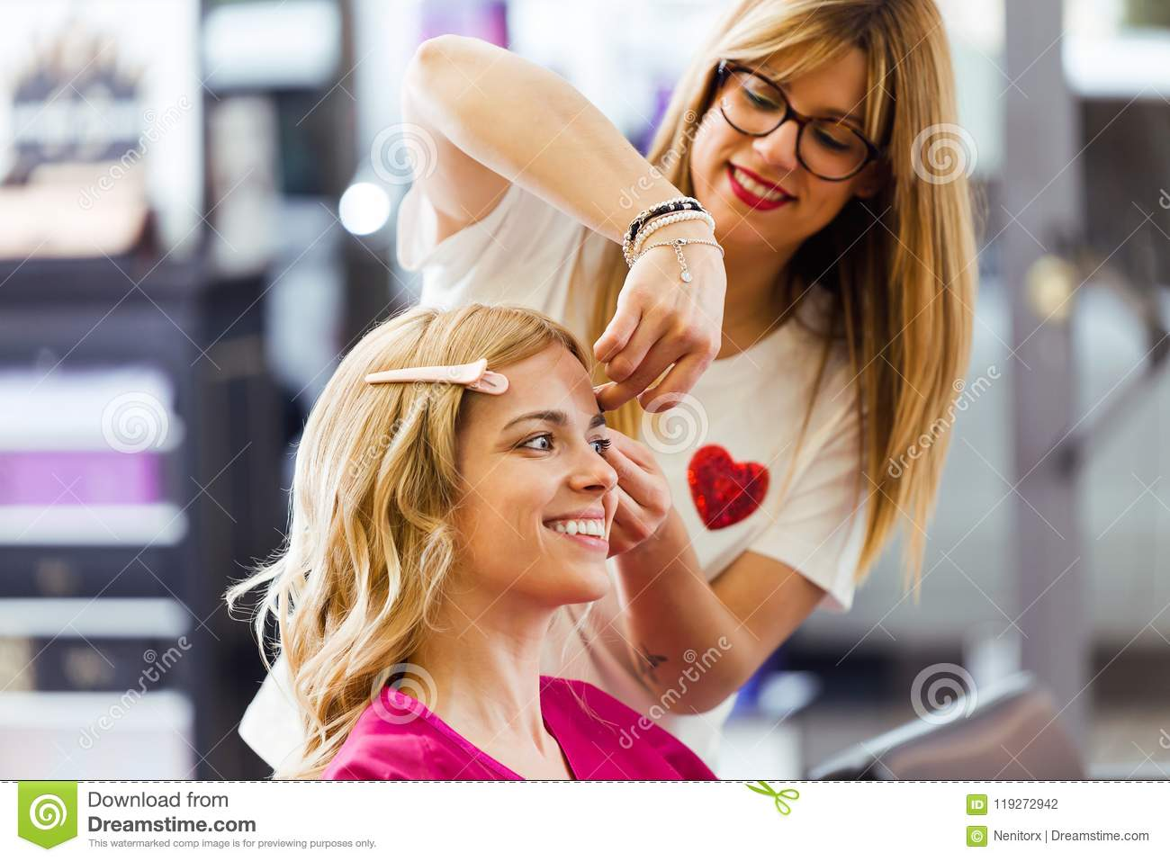 Pretty young hairdresser making hairstyle to cute woman in the beauty salon.