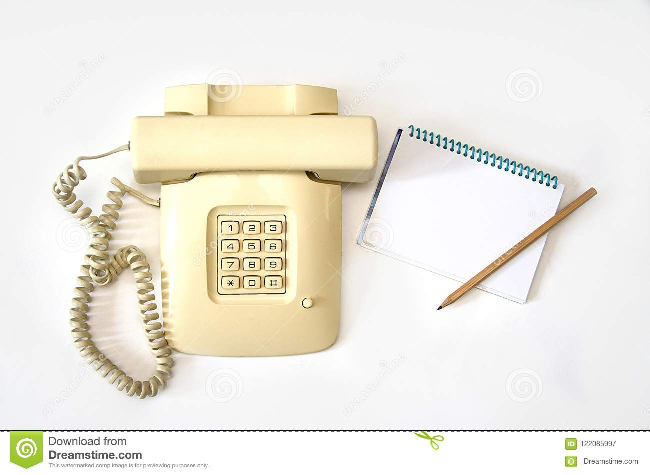 Isolate beige old telephone with wire tube lies on white background