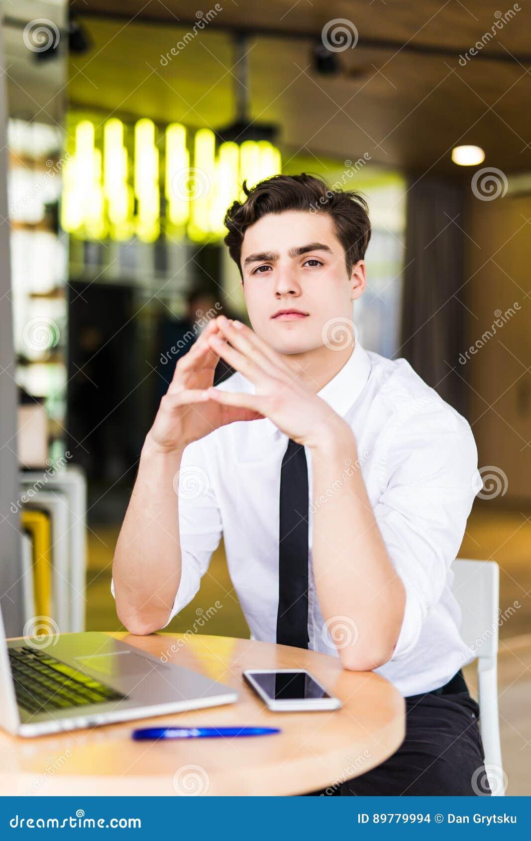 Shot Of Young Man Sitting At Table Looking At Camera And
