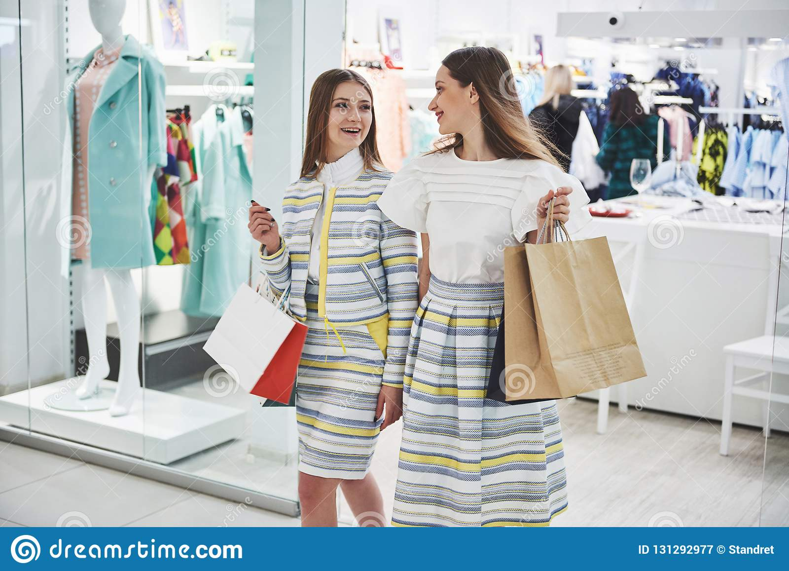 We should look at new dresses Rear view of two beautiful women with shopping bags looking away with smile while walking