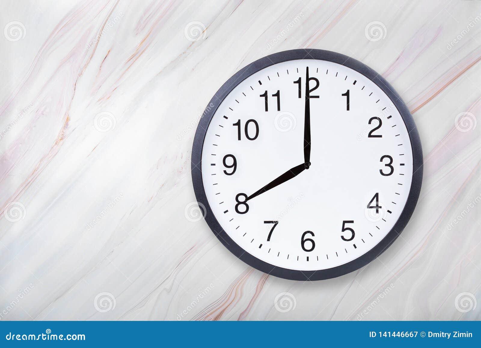 Showen för väggklockan åtta klockan marmorerar på textur Kontorsklockashow 8pm eller 8am