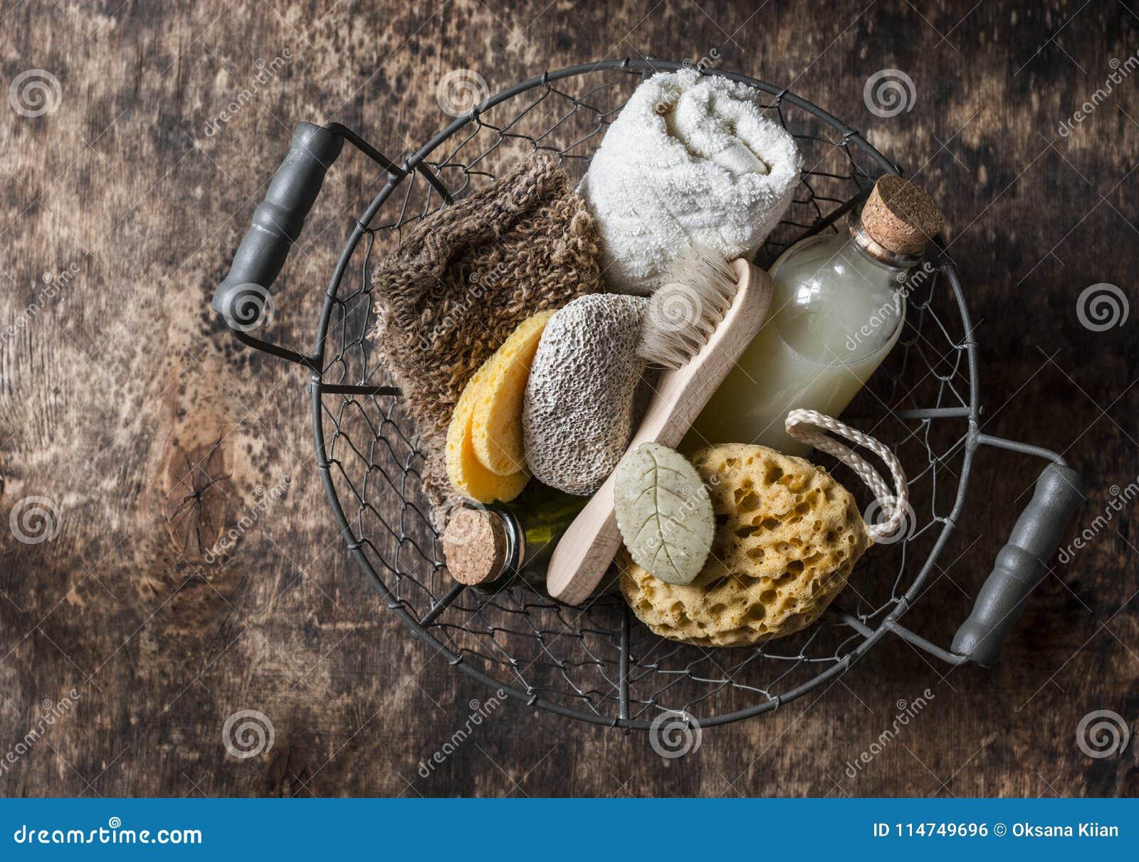 Shower accessories in vintage basket - shampoo, sponge, soap, facial brush, towel, washcloth, pumice stone. Natural beauty care pr
