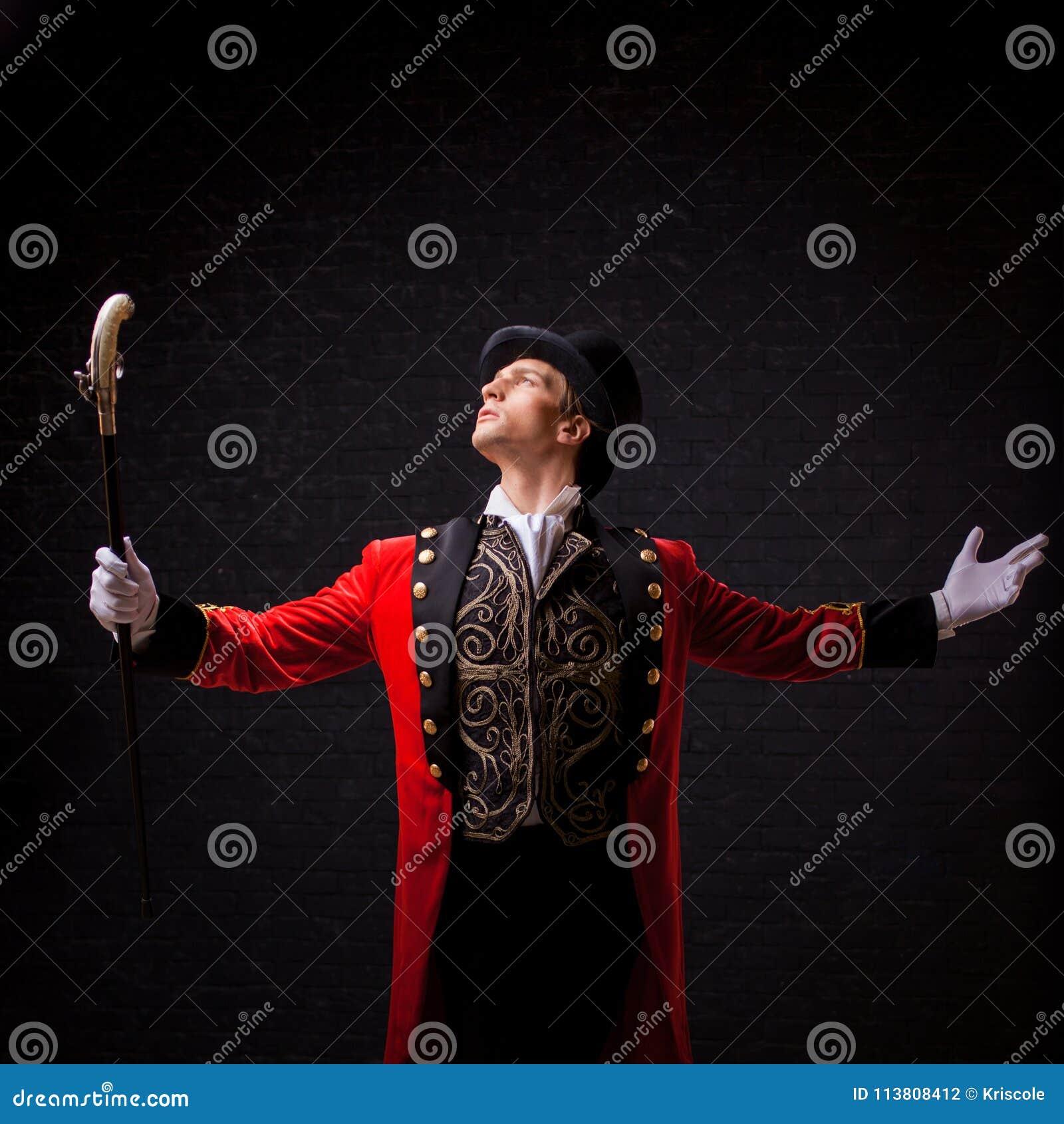 Showman Anfitrião, apresentador ou ator masculino novo na fase O indivíduo no camisole vermelho e no cilindro