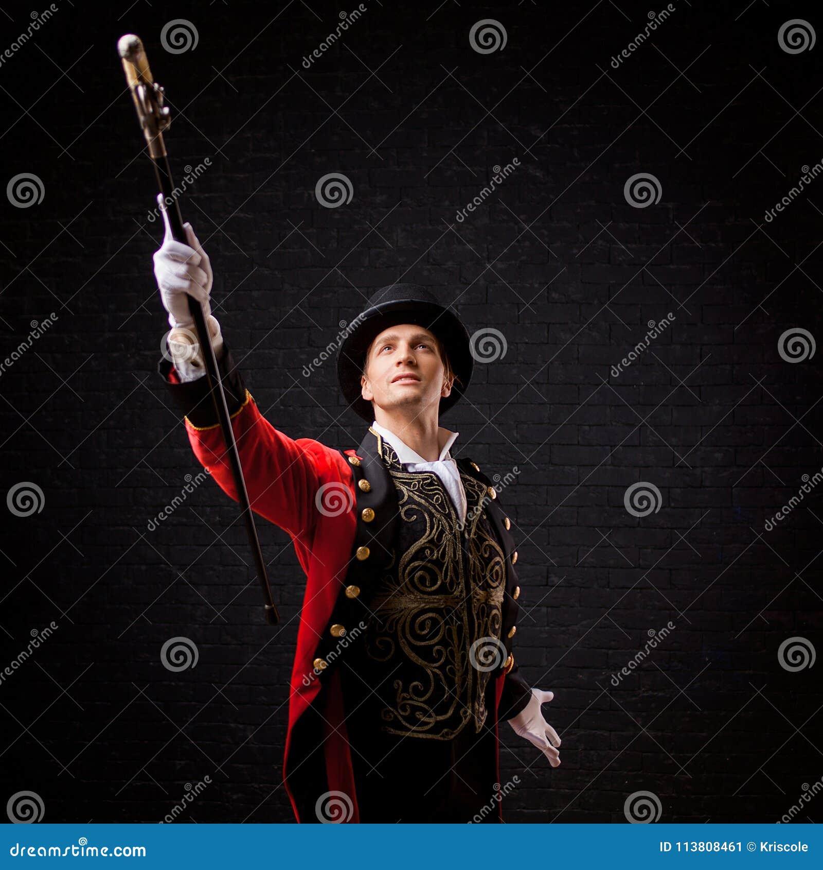 Showman Giovane anfitrione, relatore o attore maschio in scena Il camisole del tipo in rosso ed il cilindro