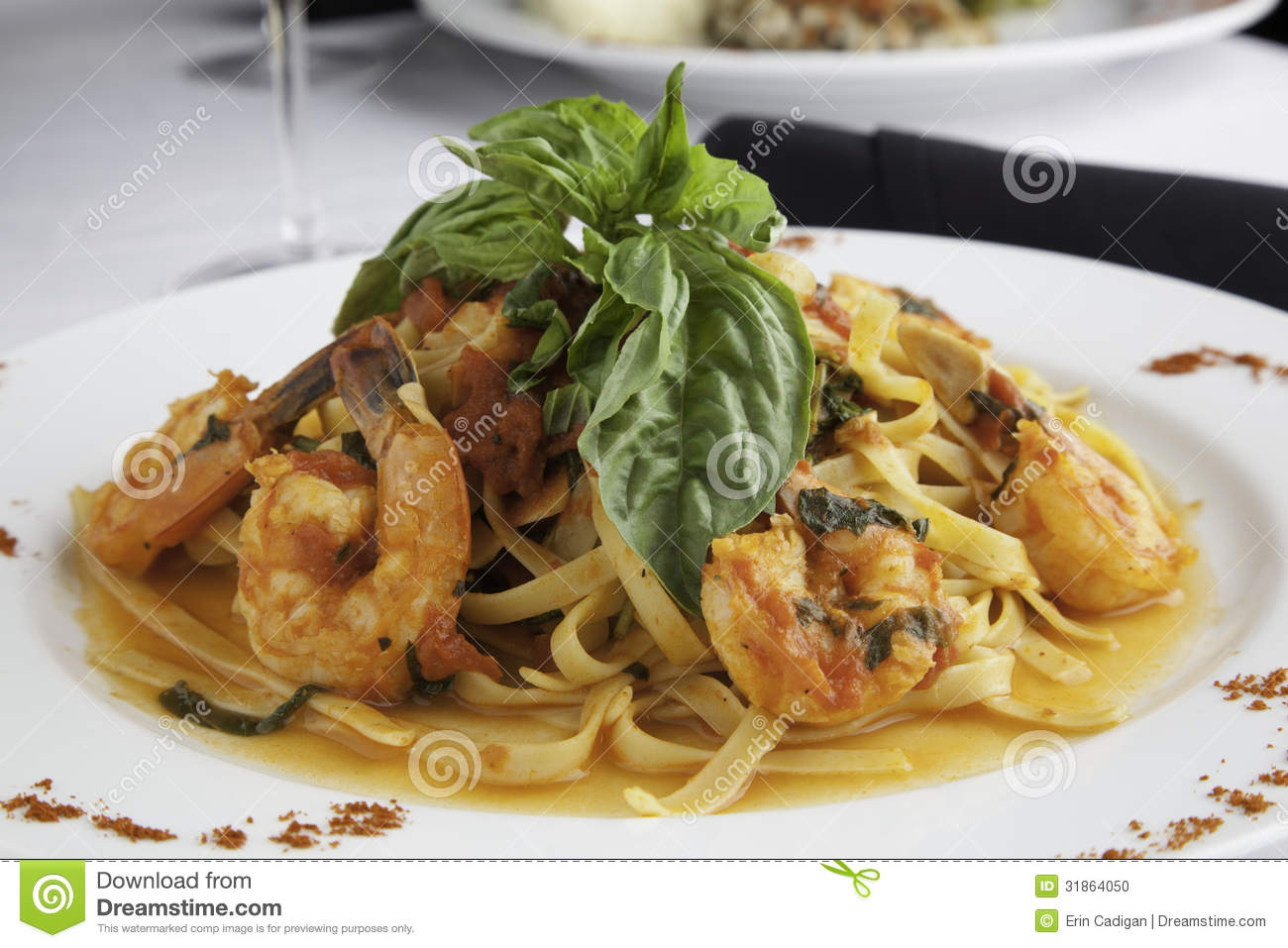 white plate holds linguine with shrimp in a fra diavolo sauce ...