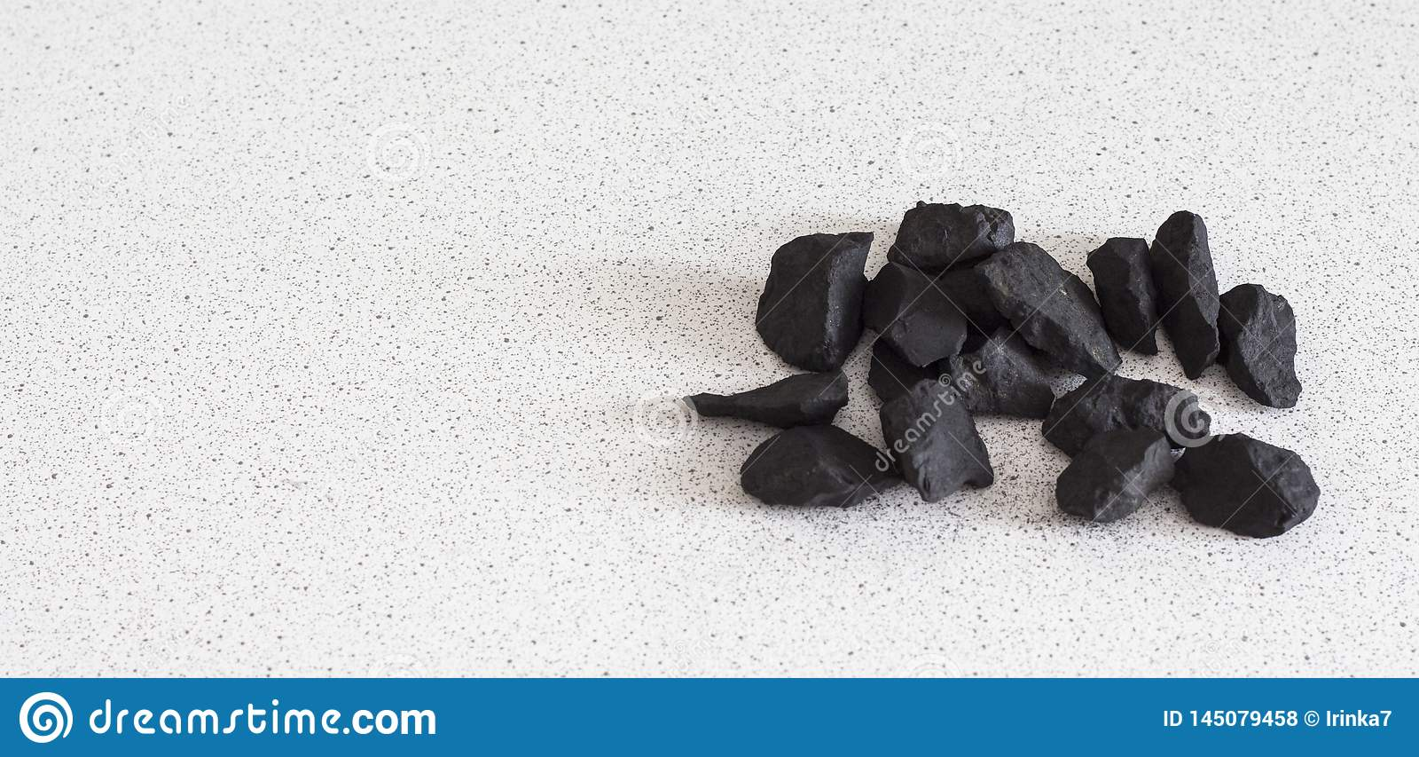 Shungite stones on white background with copy space