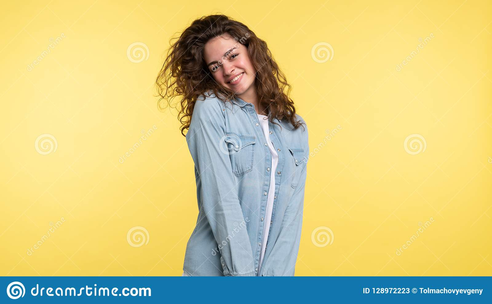 Pretty shuy brunette woman with curly hair over yellow background