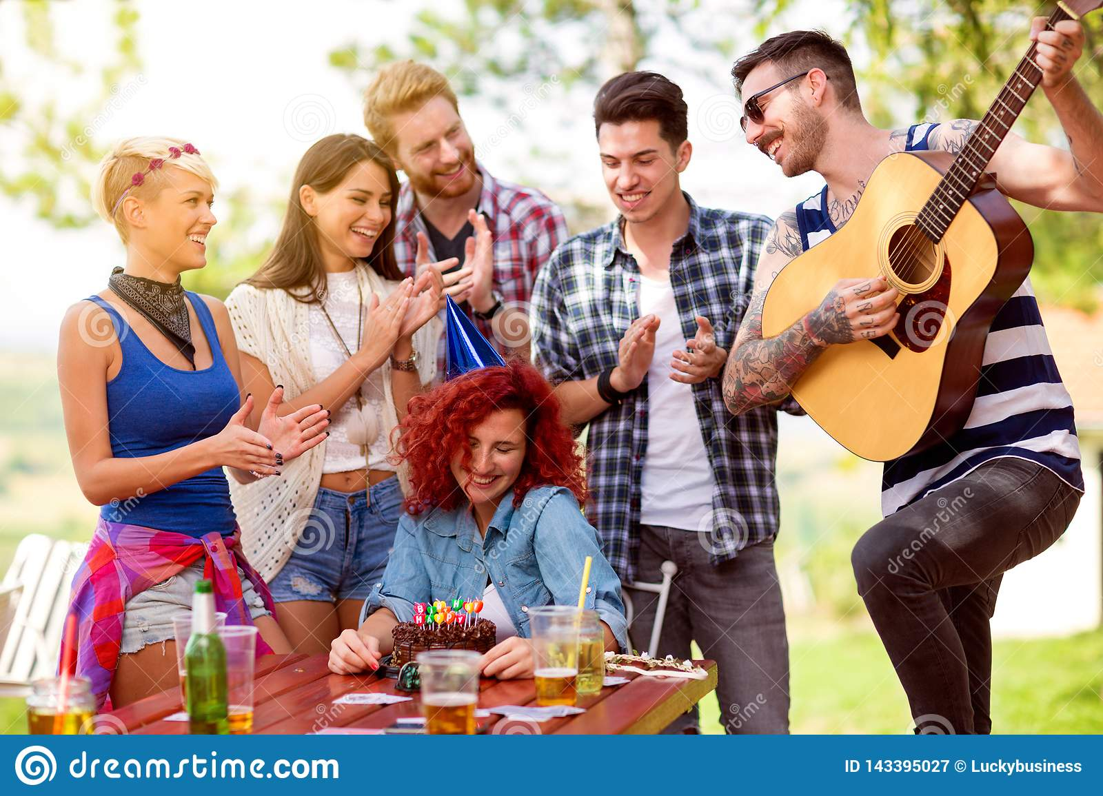Shy birthday girl with friends who applaud and plays birthday song at guitar