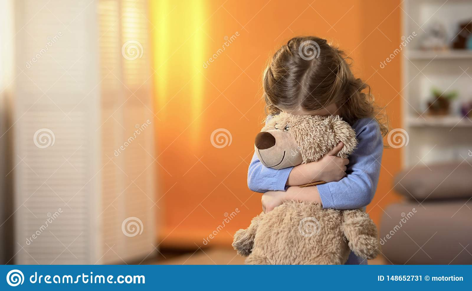 Shy curly girl hiding face behind favorite teddy bear, childhood psychology