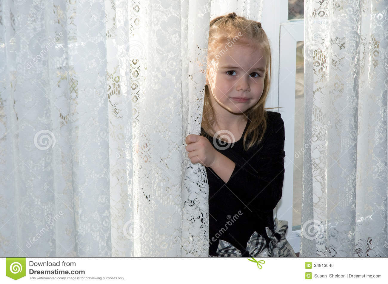 little girl peeks shyly out from behind a white lace curtain.